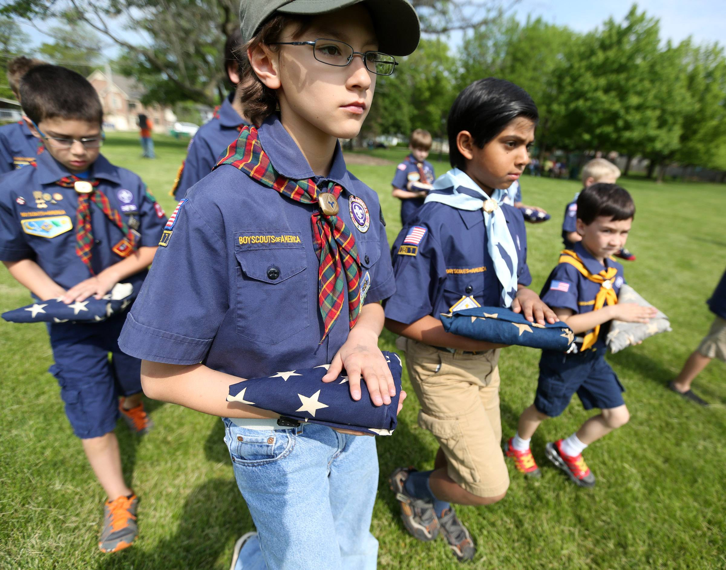 Boy Scouts Ryan Conwell, center, and Rahil Patel with Pack 12 march with folded American flags at flag retirement ceremony held by Bartlett VFW Post 11018 and American Legion Post 1212 at Bartlett Park on Memorial Day.