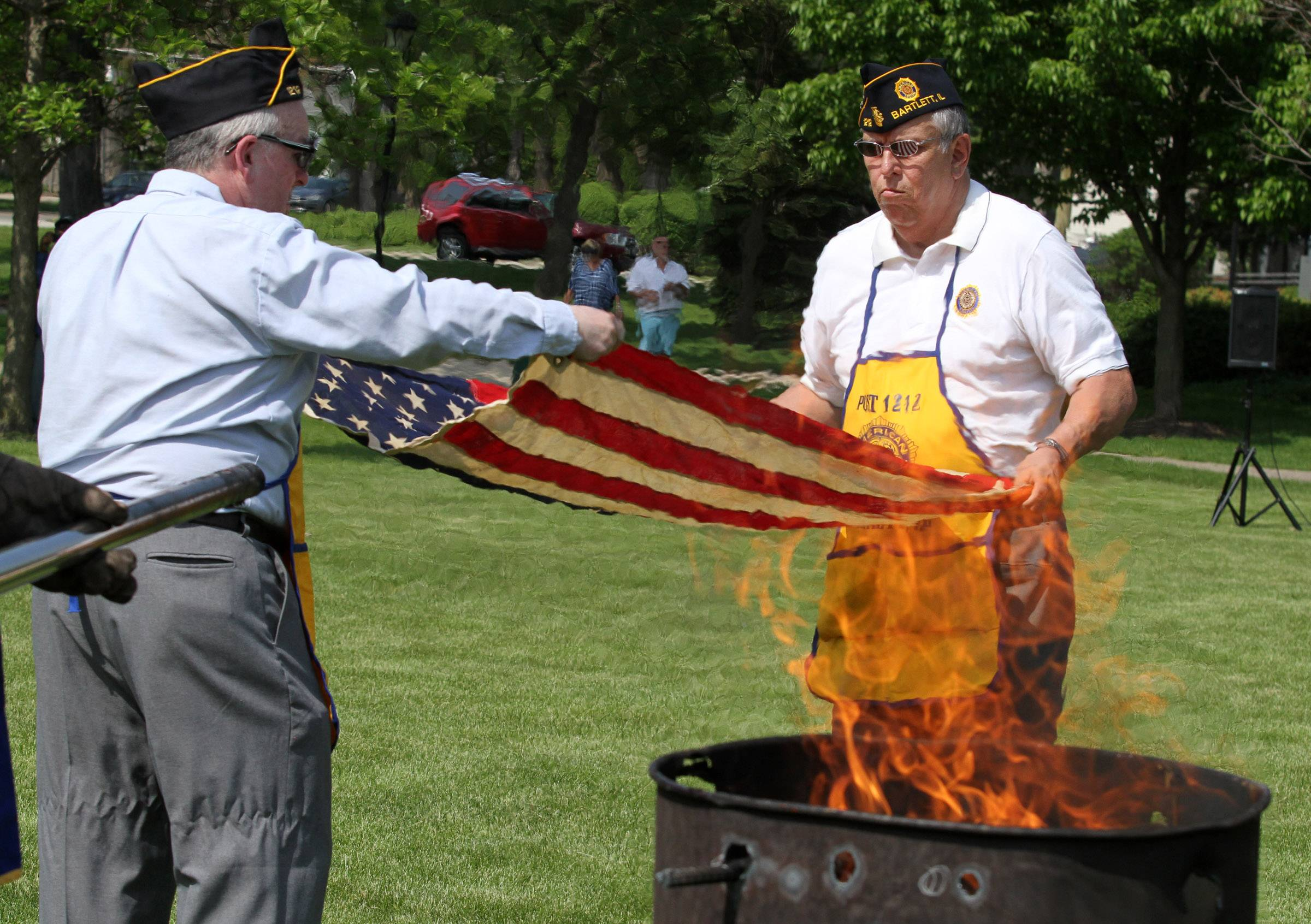Paul Miller of Hanover Park and Bob Vaca of Bartlett, both with American Legion Post 1212, unfold a worn American flag to be burned during a flag retirement ceremony held by Bartlett VFW Post 11018 and American Legion Post 1212 at Bartlett Park on Memorial Day.