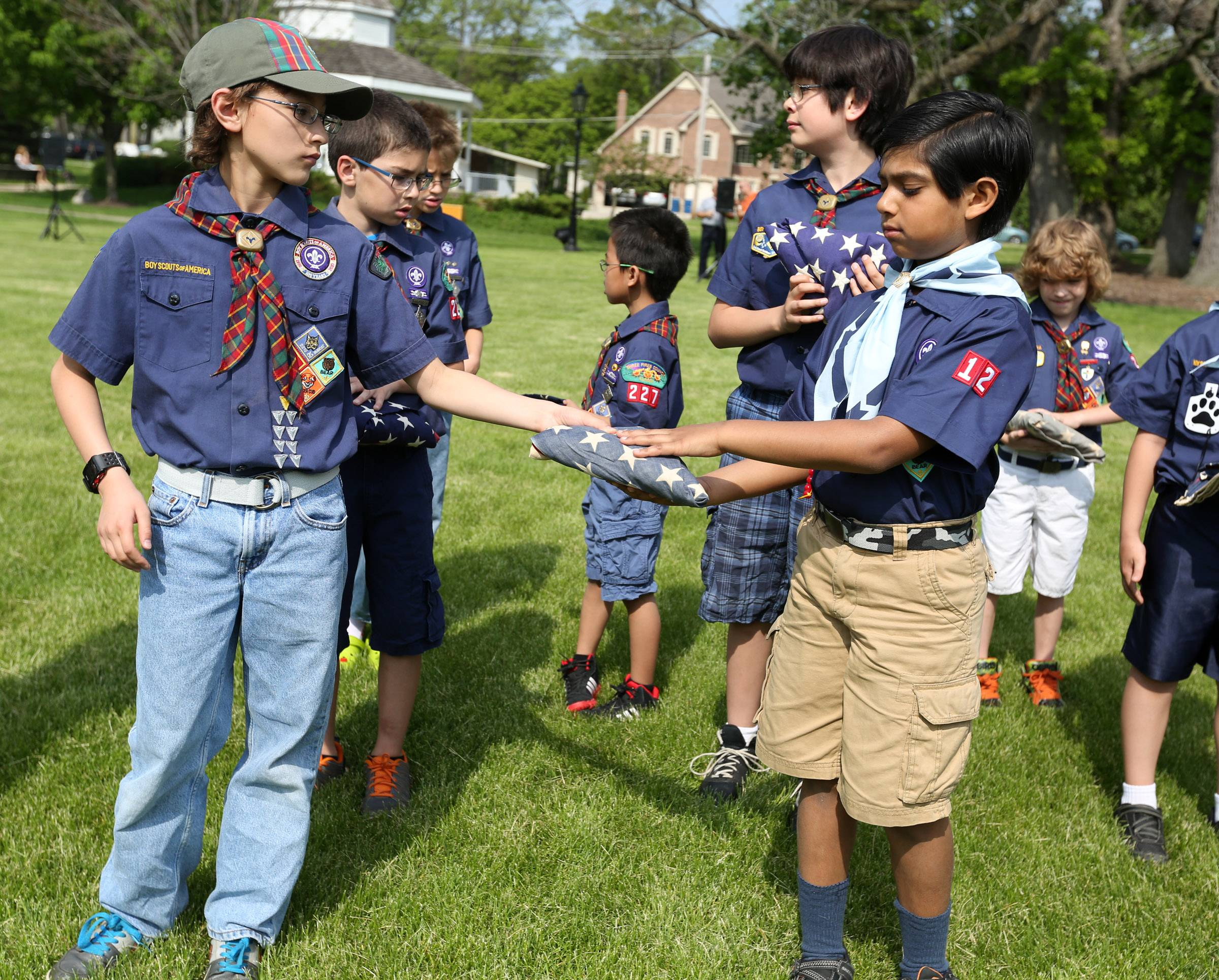 Boy Scout Ryan Conwell hands a folded worn American flag to Rahil Patel, both with Pack 12, to start a flag retirement ceremony held by Bartlett VFW Post 11018 and American Legion Post 1212 at Bartlett Park on Memorial Day.