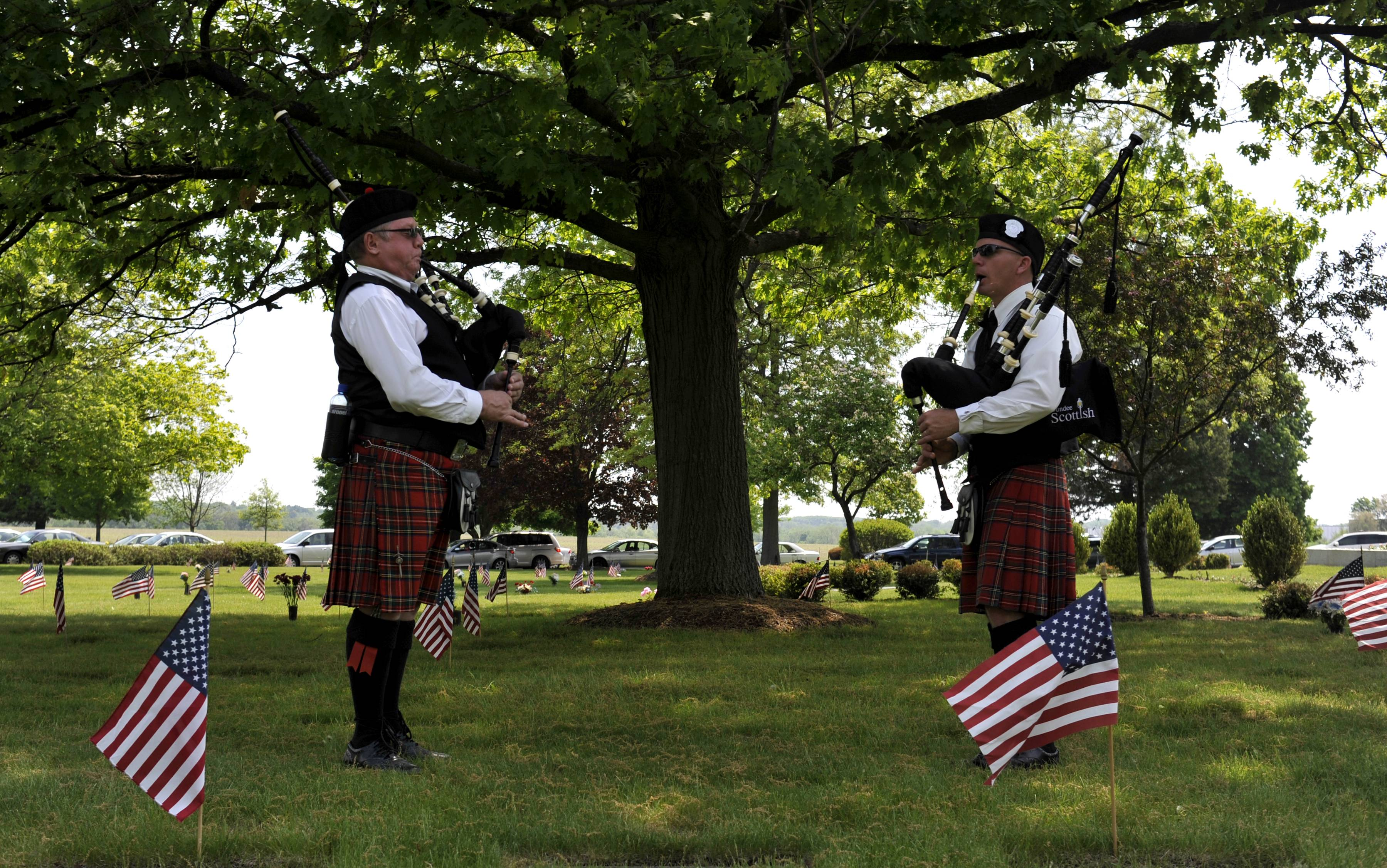Mark Kilgore of Carol Stream (left) and John Cunningham of Elgin (right) play bagpipes before the start of the Memorial Day Service at River Valley Memorial Gardens in West Dundee on Monday, May 26. Kilgore and Cunningham are members of the Dundee Scottish Pipe Band.