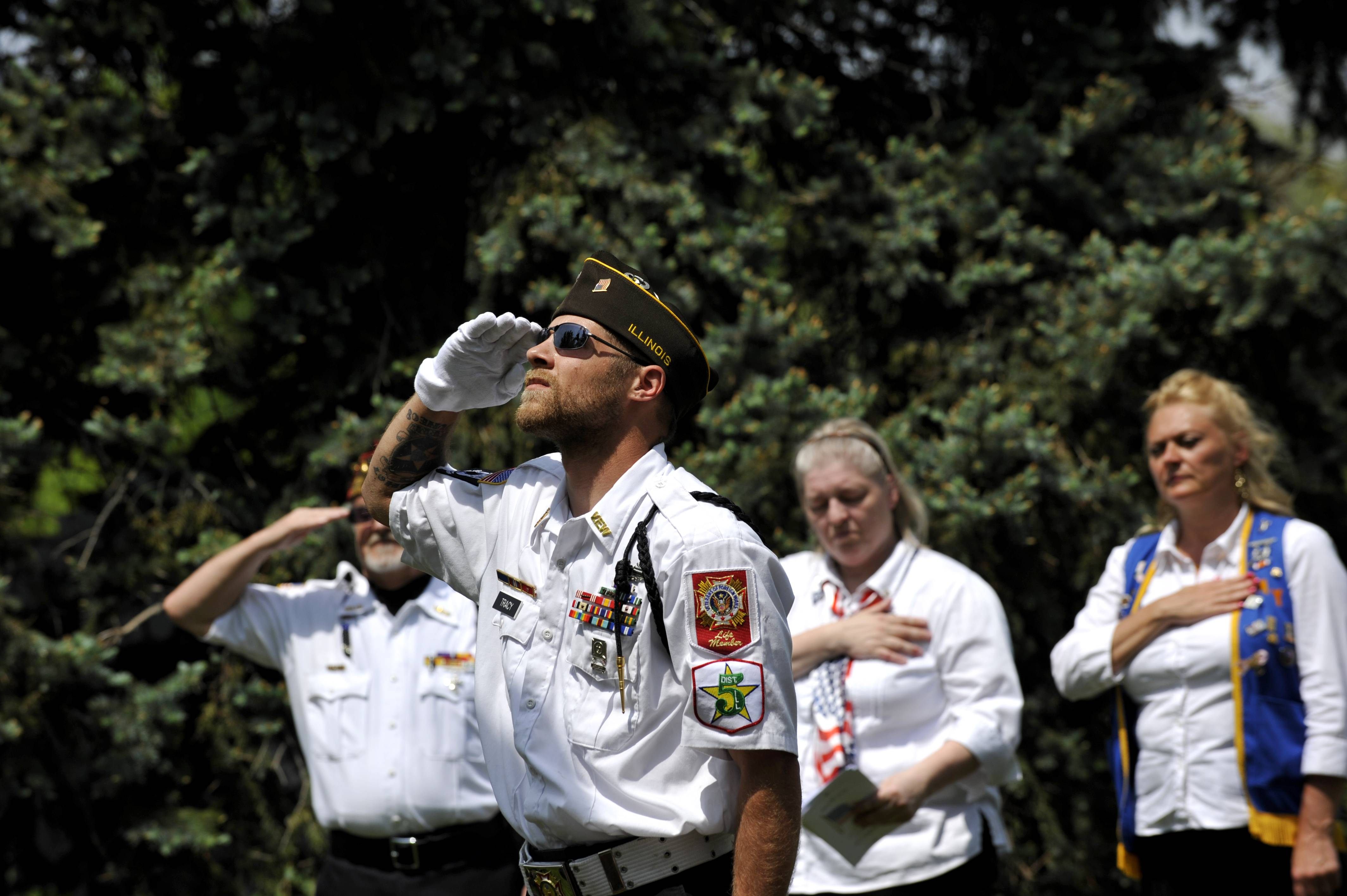 Adam Tracy of West Dundee gives salute during the Memorial Day Service at River Valley Memorial Gardens in West Dundee on Monday, May 26. Patrick Green of Carpentersville, Jessica Gospodarek of Carpentersville, and Amy Lessing of Elgin are pictured in the background (left to right).