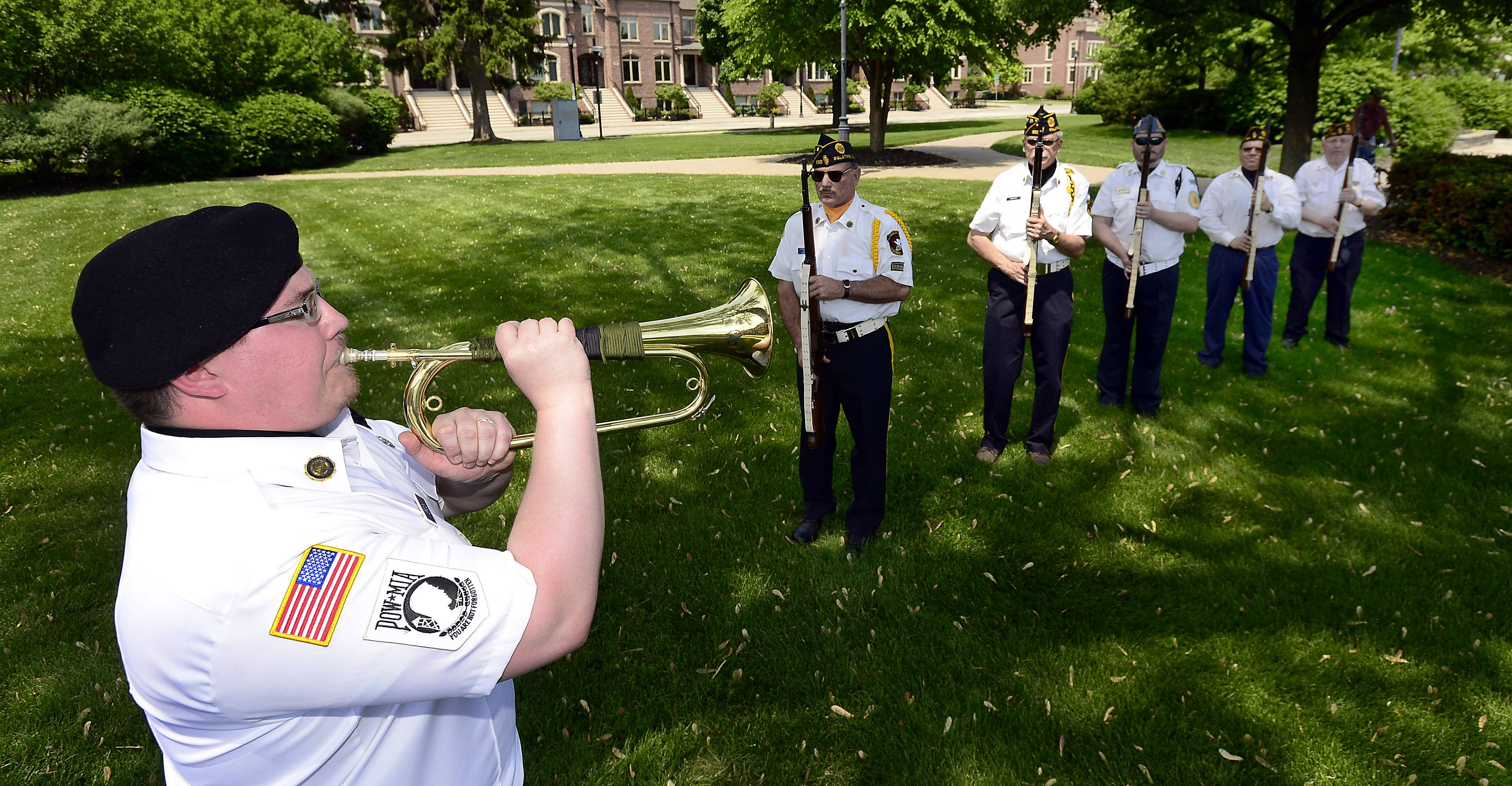 Jonathan Brock of Palatine's American Legion Post 690 sounds taps at the Memorial Day service at the Towne Square in Palatine on Monday.