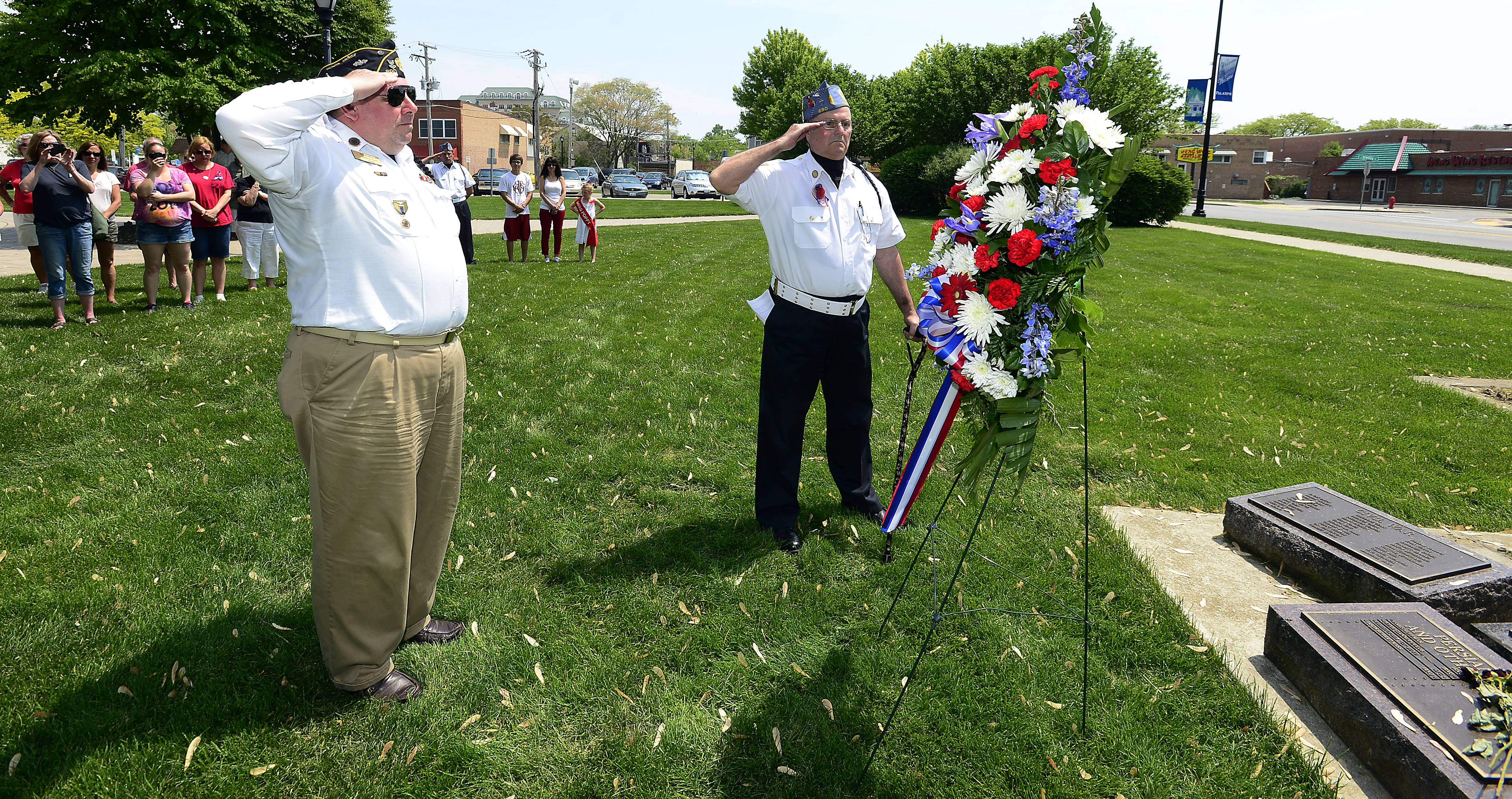 Commander Ed Grabowski (left) and Chaplain Tom Seick of Palatine's American Legion Post 690 salute after the laying of the wreath at the Memorial Day service at the Towne Square in Palatine on Monday.
