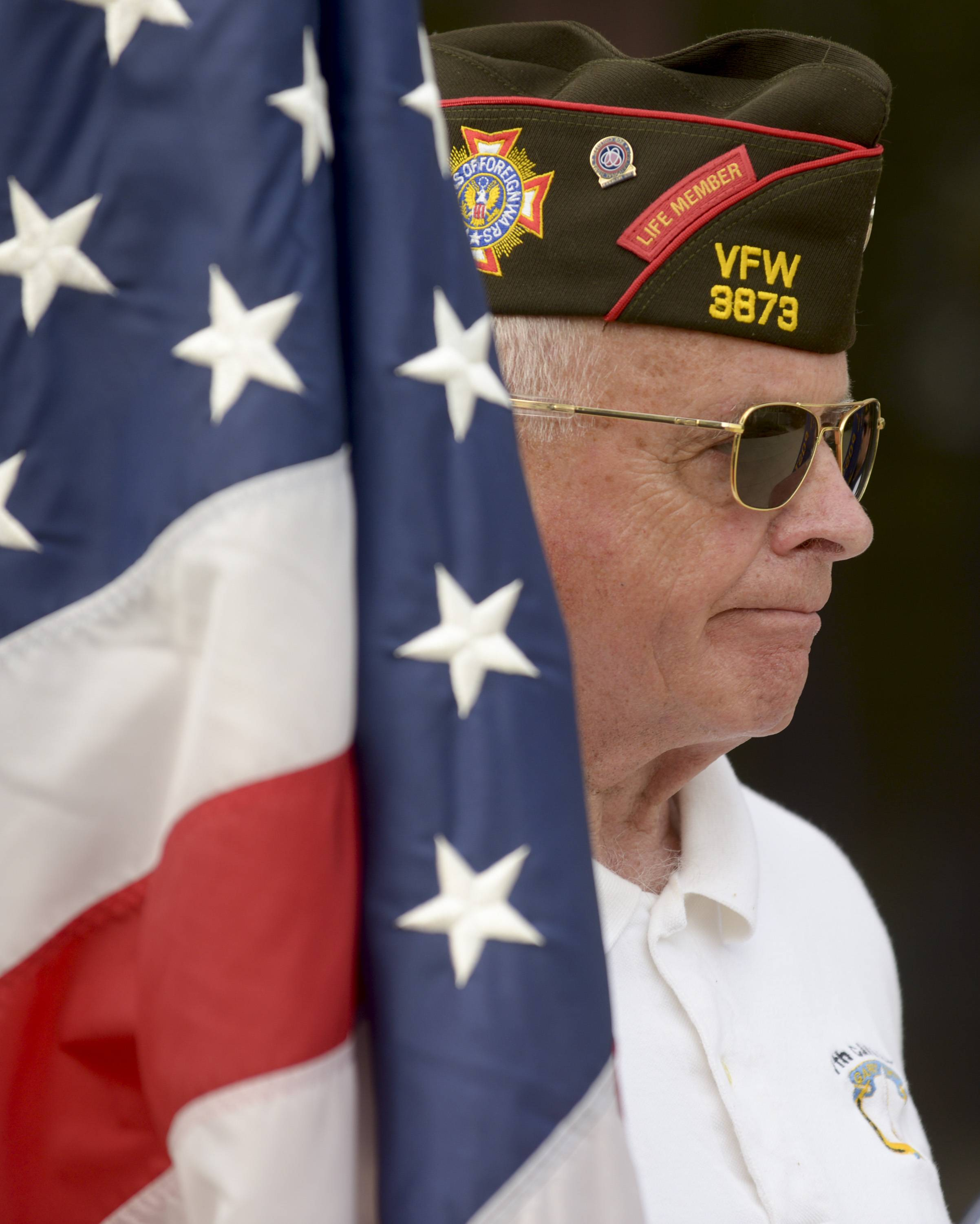 Vietnam Army veteran and VFW 3873 member Mike McGrath carries the American Flag during Naperville's Memorial Day service at the Cmdr. Dan Shanower/Sept. 11 memorial, Monday.