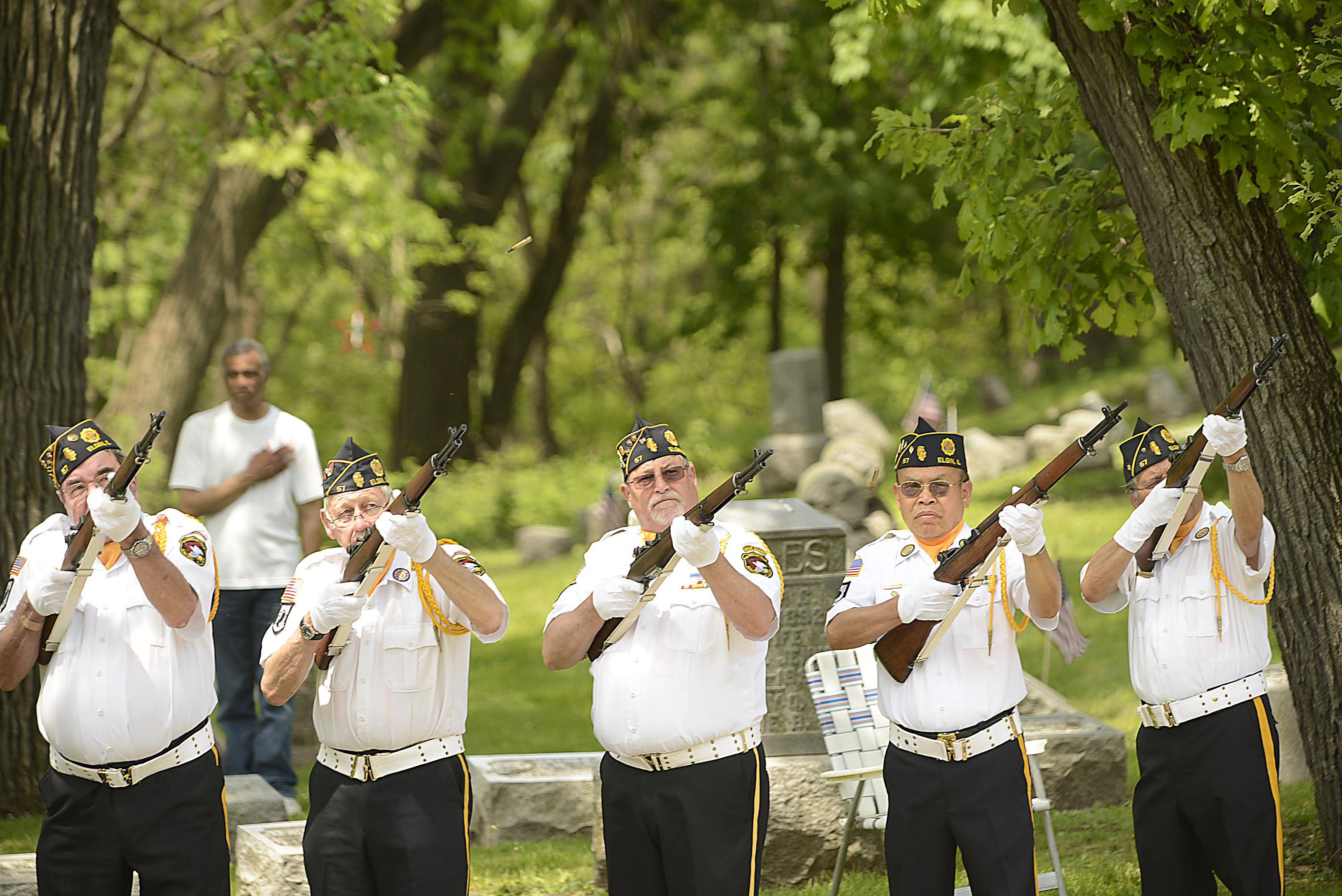 A combined Color Guard fires a rifle salute at the end of the Elgin Memorial Day event at Bluff City Cemetery Monday.