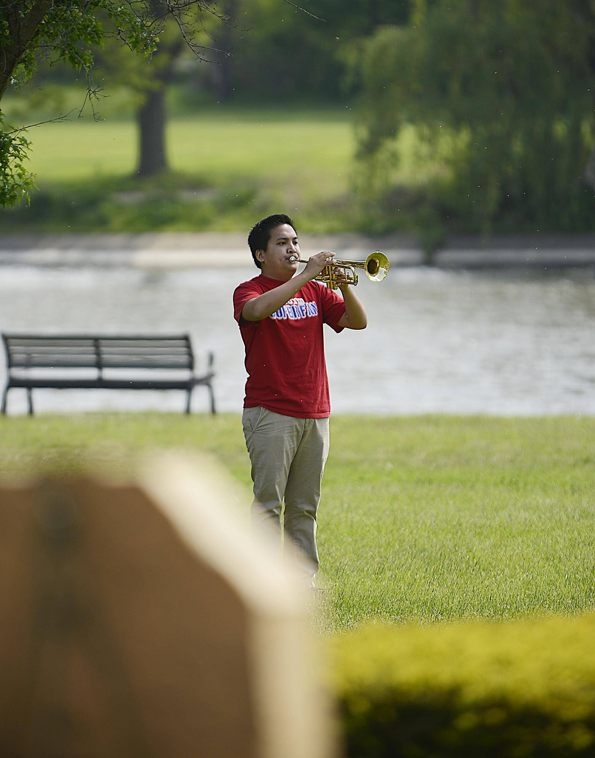 Ian Dela Merced, a senior at South Elgin High School, plays Taps to close the South Elgin Memorial Day event at Panton Mill Park Monday.