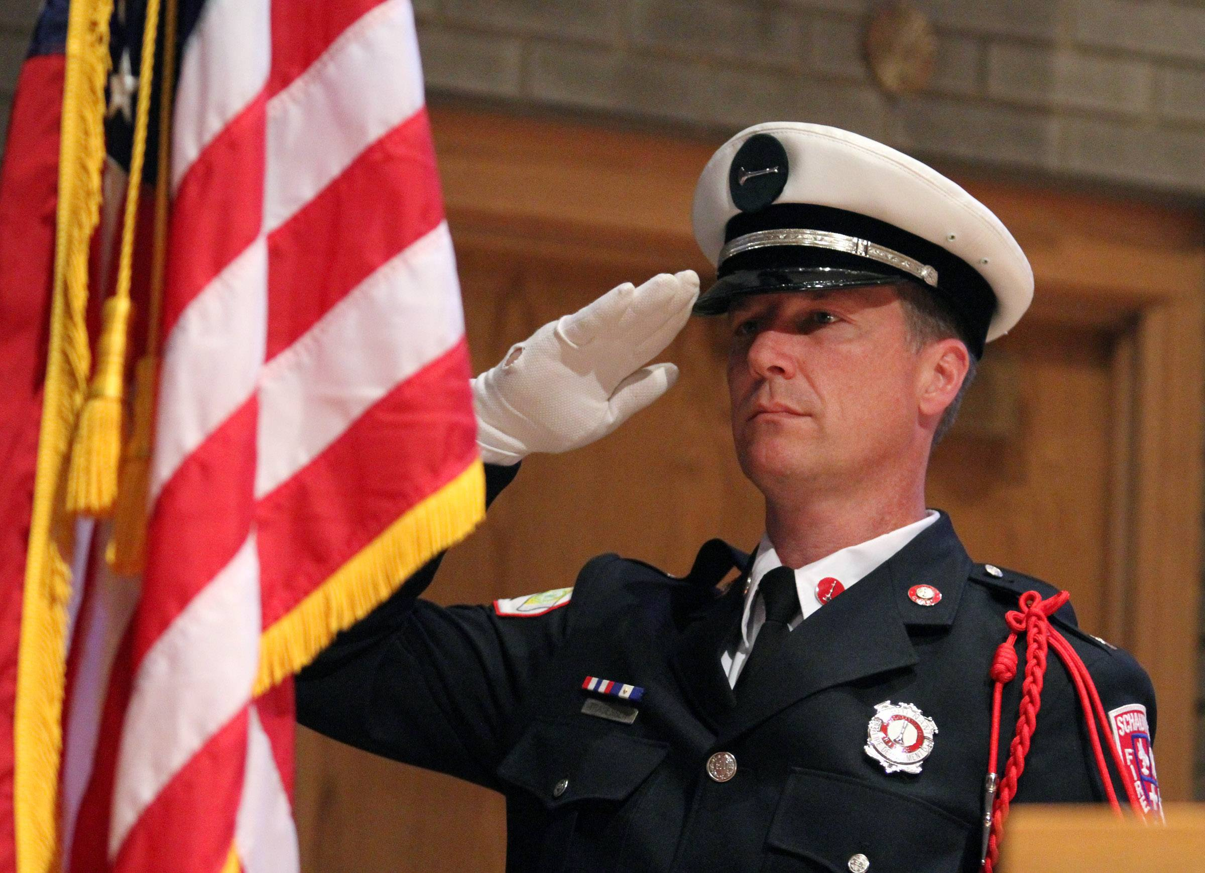 Doug Tragesser, Schaumburg Fire Department, salutes the American Flag during a Memorial Day ceremony at St. Peter Lutheran Church in Schaumburg.