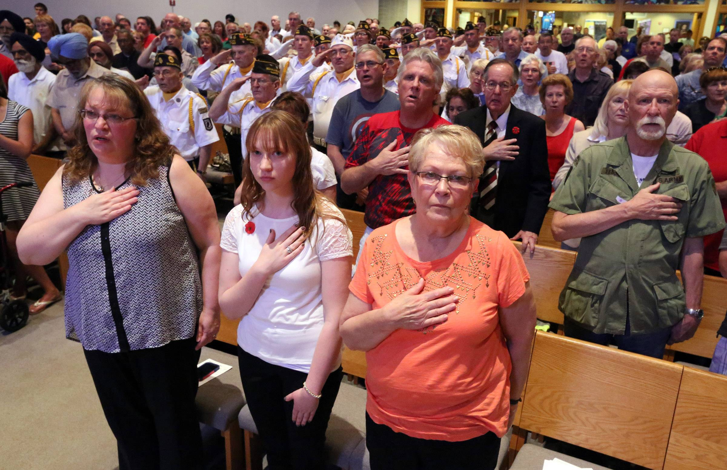 Attendees of a Memorial Day ceremony hold their hands on their hearts during the Pledge of Allegiance at St. Peter Lutheran Church in Schaumburg.