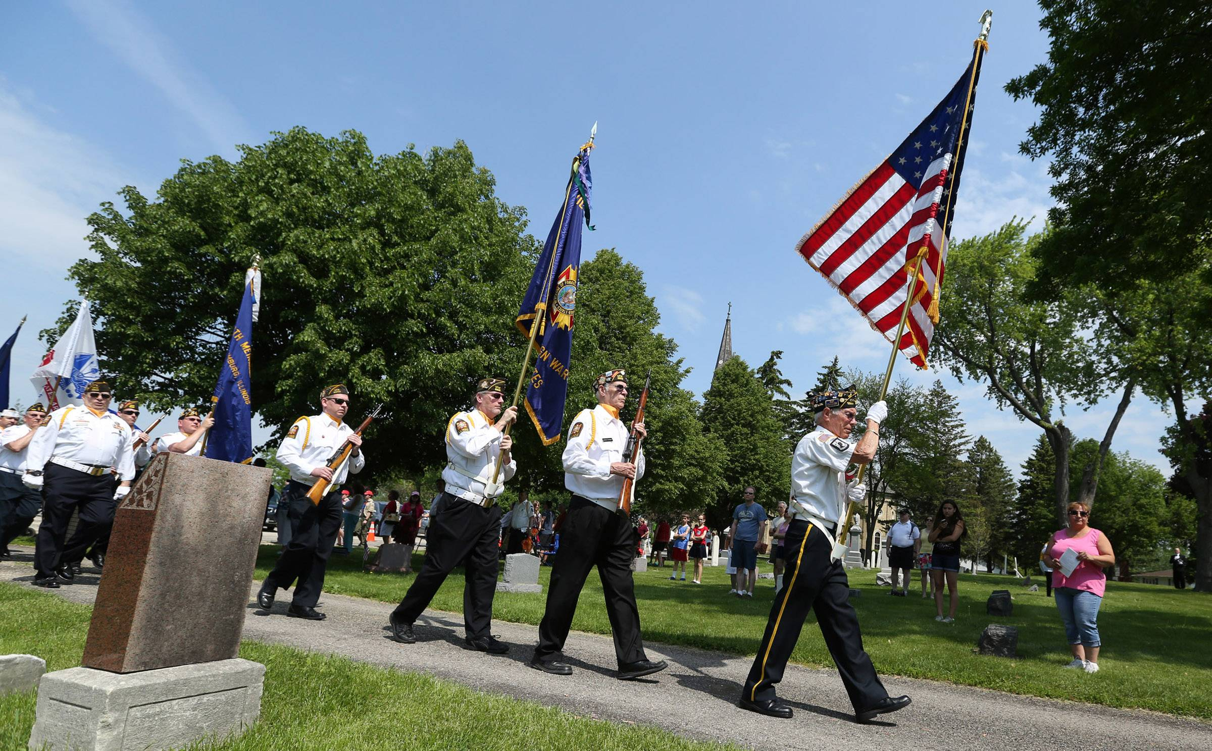 Pete Justen with American Legion 1983 carries the American flag as he leads a color guard into St. Peter Lutheran Cemetery for a Memorial Day ceremony in Schaumburg.