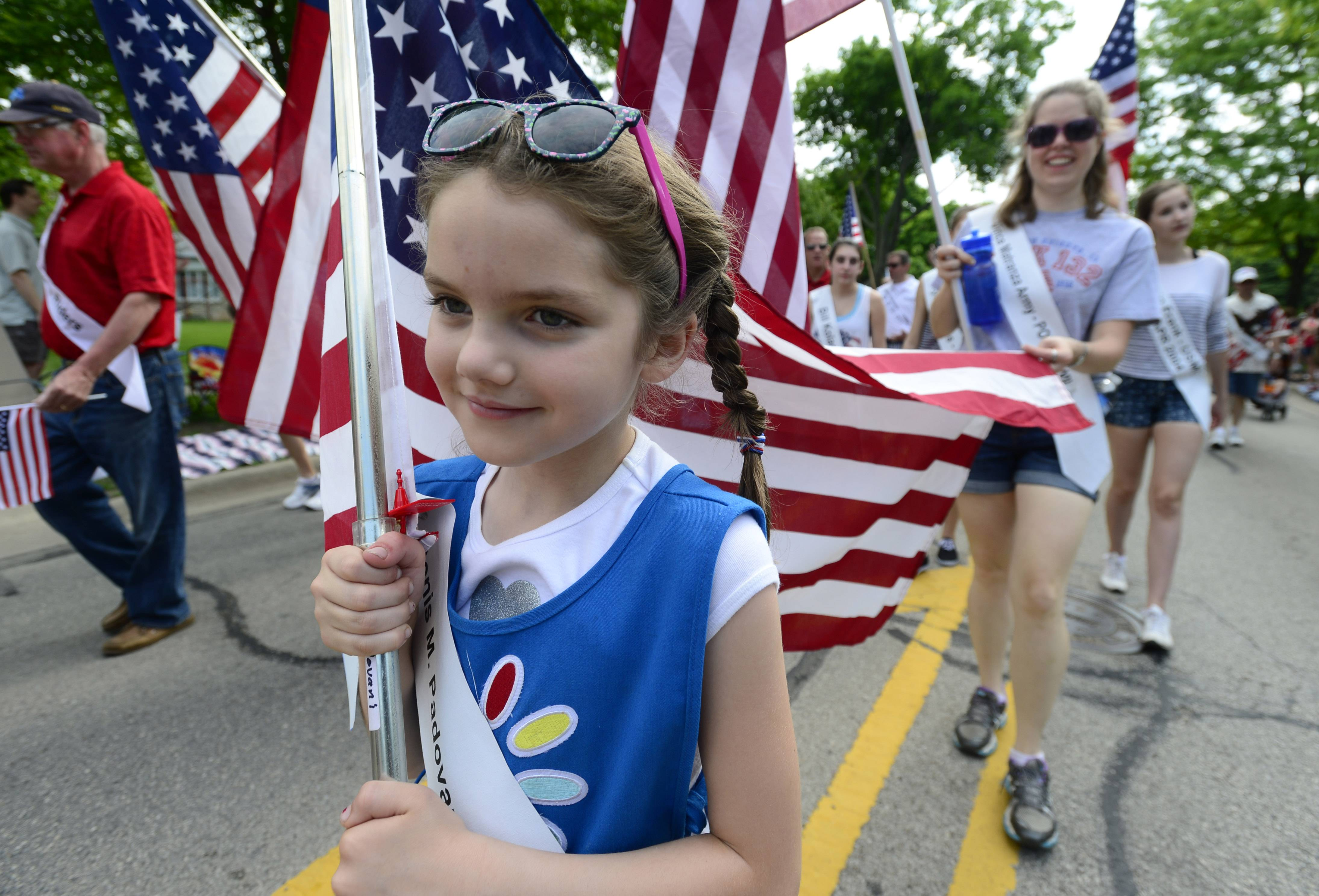 Emily Pawlak, 7, of Arlington Heights honors veterans by carrying the flag during the parade at the Arlington Heights Memorial Day event on Monday.