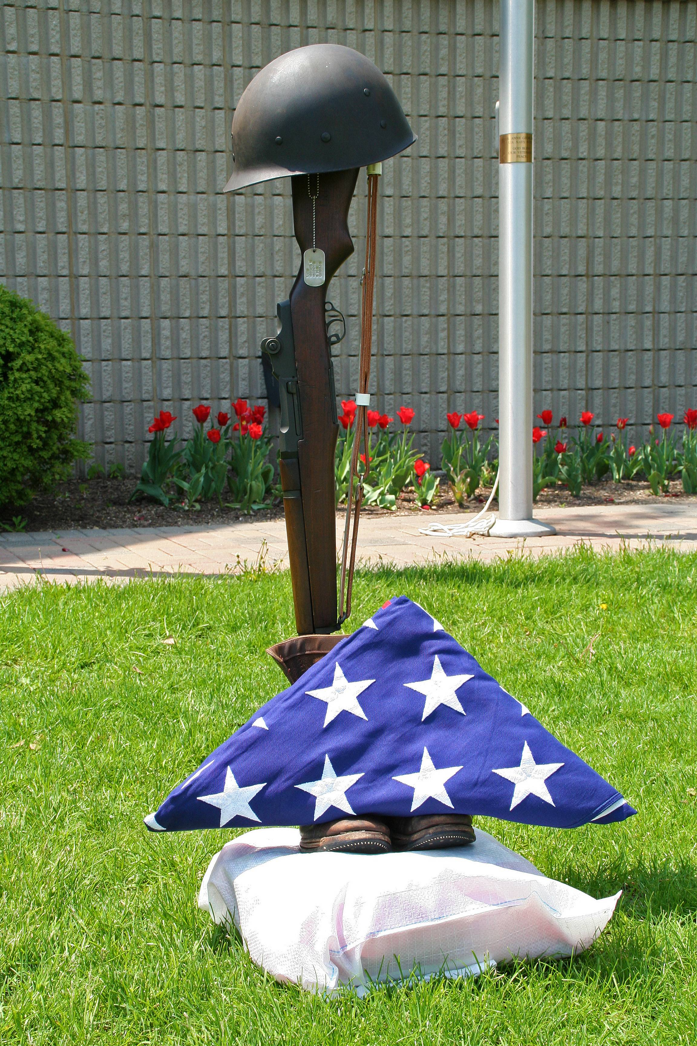 The Battlefield Monument, built by Sergeant Richard E. Ohman from a rifle, dog tags, helmet, boots, and the American Flag, at the Memorial Day Ceremony at the Lake Park Memorial Pavilion on May 26.