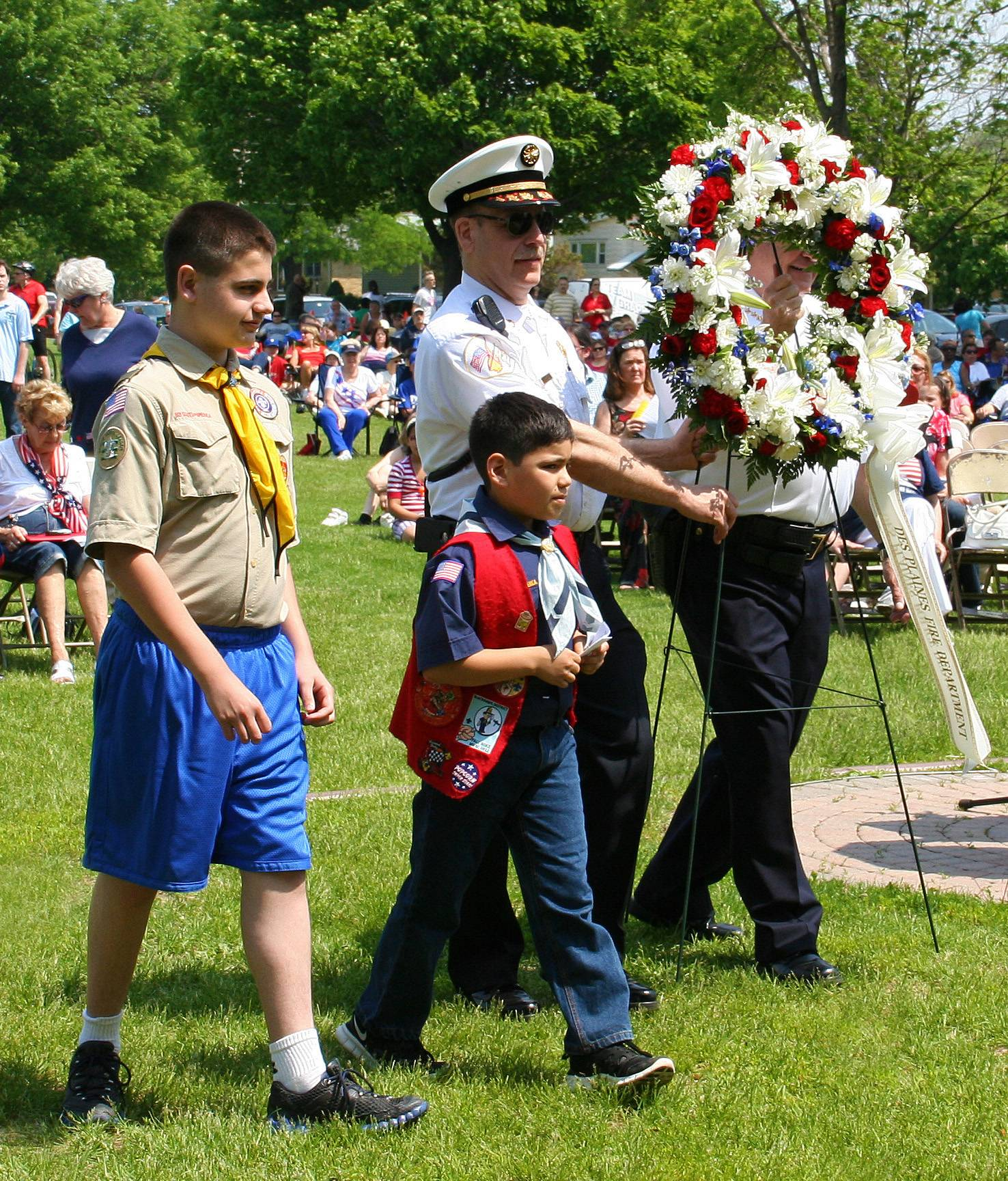 Fire Chief Alan Wax and Police Chief William Kushner, accompanied by a Boy Scout and Cub Scout, during the Presentation of the Wreaths at the Memorial Day Ceremony on May 26 at Lake Park.