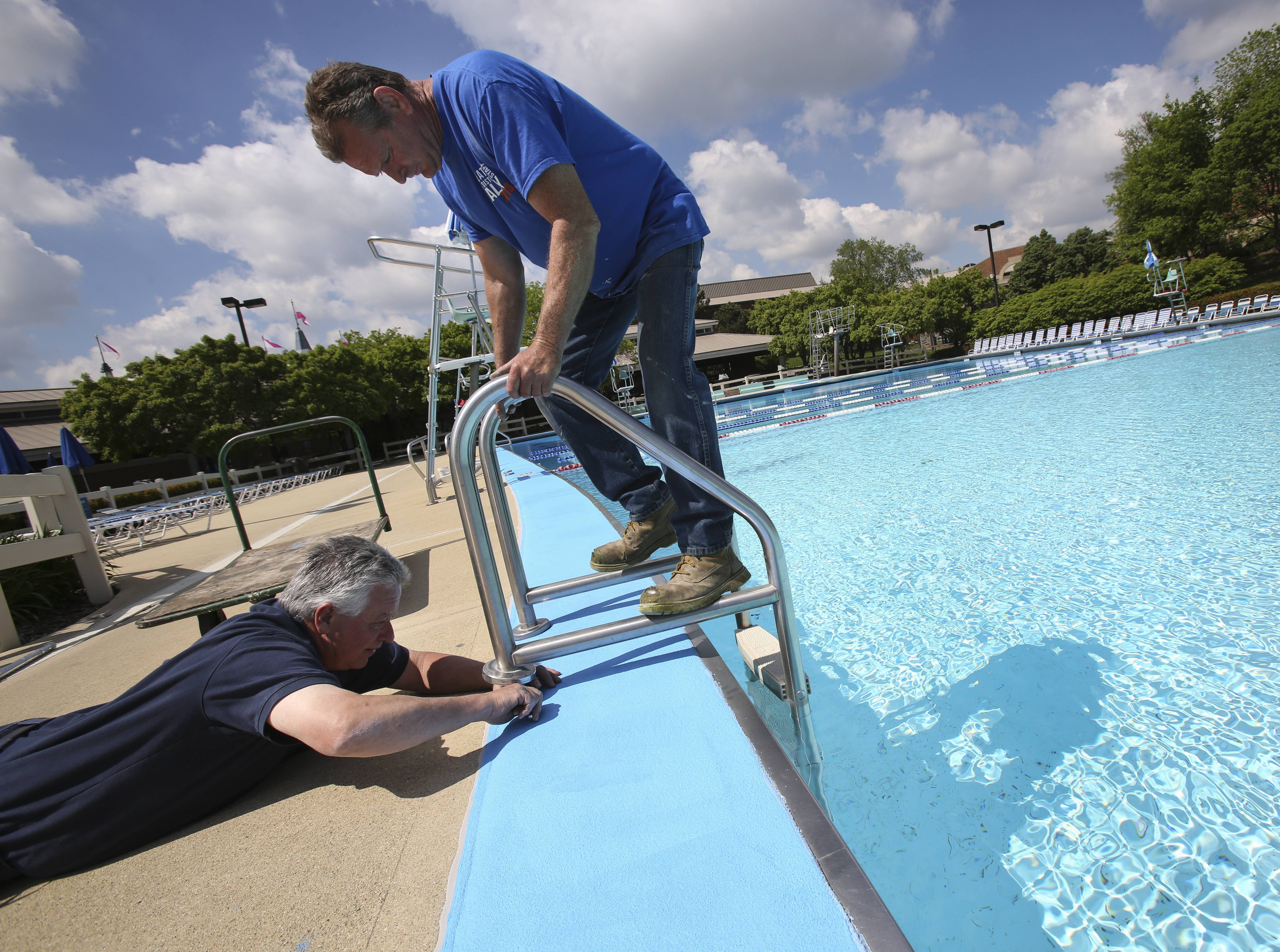 Don Shee, left, and Dan Saxton, right, with the Wheaton Park District, put a ladder into Rice Pool on Friday in preparation for Saturday's opening day.