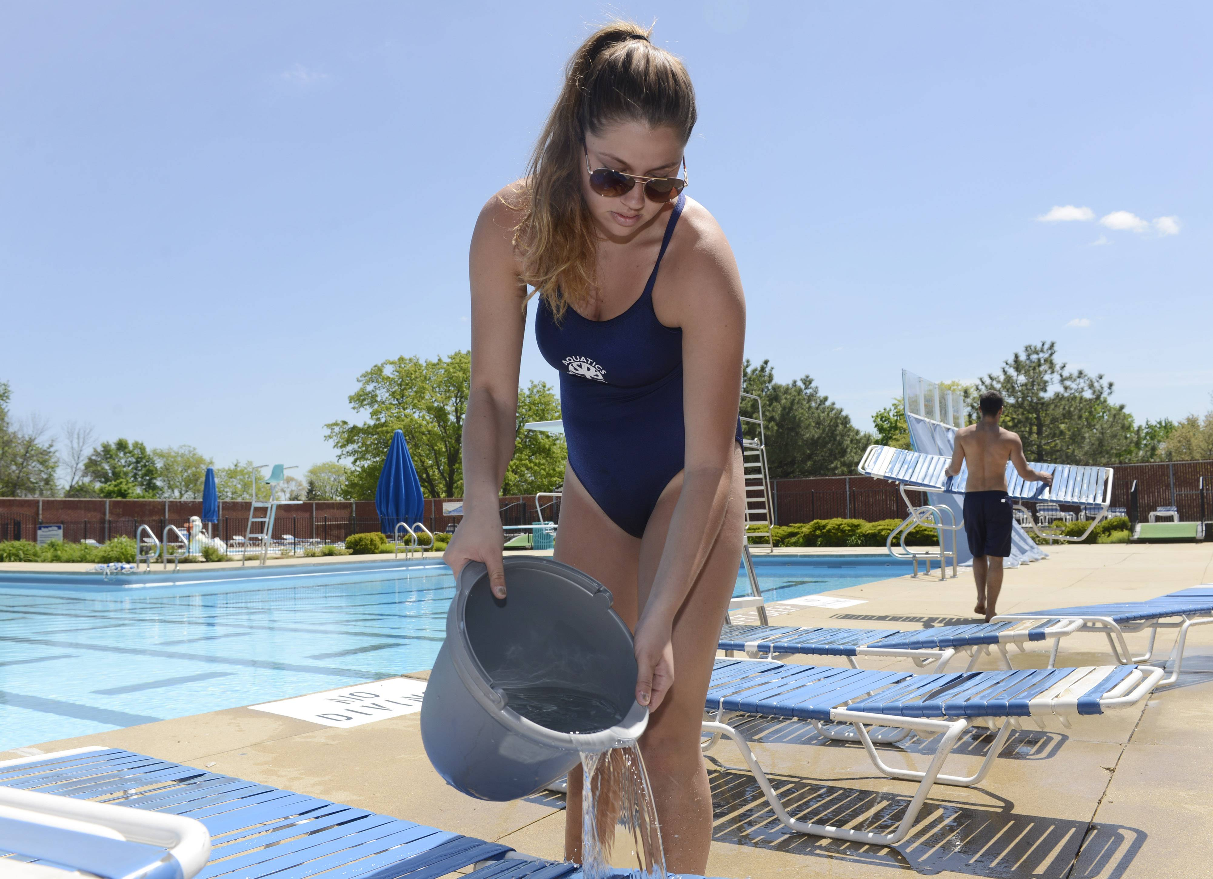 Lifeguard Ema Cigerova helps clean chairs Friday afternoon in preparation for Saturday's opening of the Schaumburg Park District's Bock Neighborhood Center and Park pool Friday.