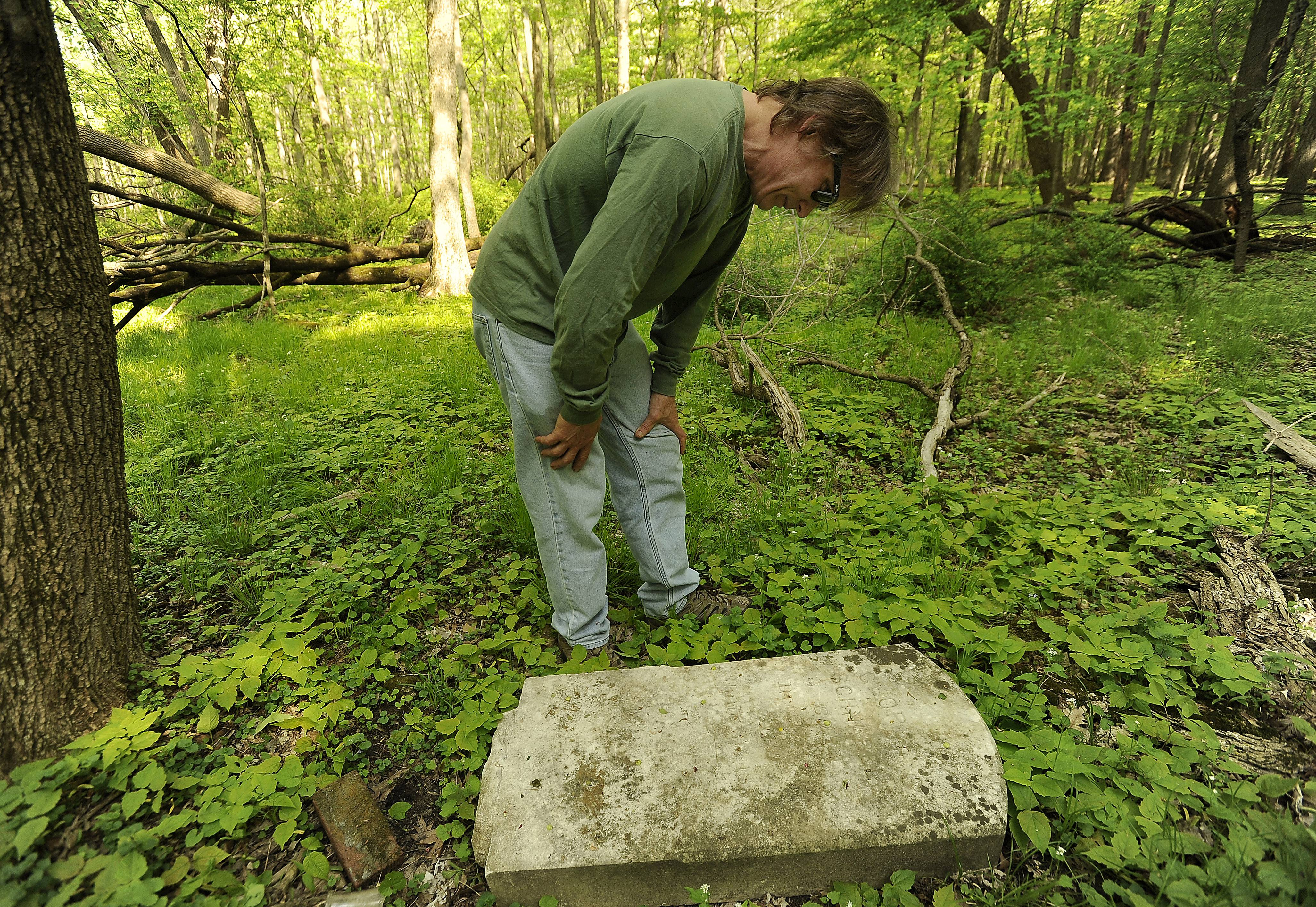 Joel Schauer, of Hawthorn Woods, checks out the tombstone of George S. Schnabele that he stumbled across one day as he and his family were out bird watching. His mission was to return the tombstone to its original resting spot and he was surprised to find that this was the final resting place.
