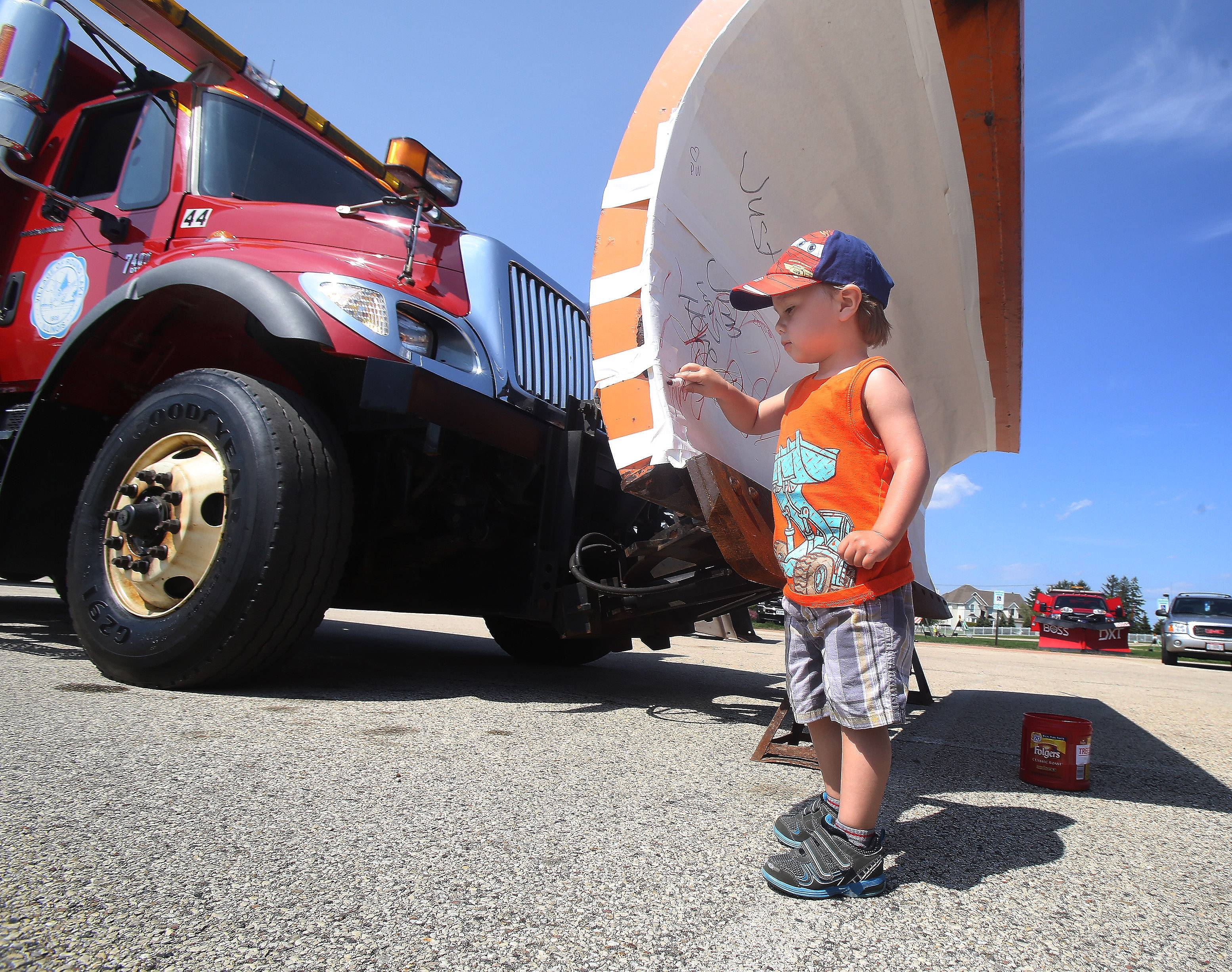Two-year-old Gabriel Nieto, of Round Lake, draws on a snow plow during the first Round Lake Public Works Open House Wednesday. The event featured vehicles from the public works department, the Round Lake Police Department, the Round Lake Area Fire Protection District, and the Lake County Public Works and Lake County Transportation.