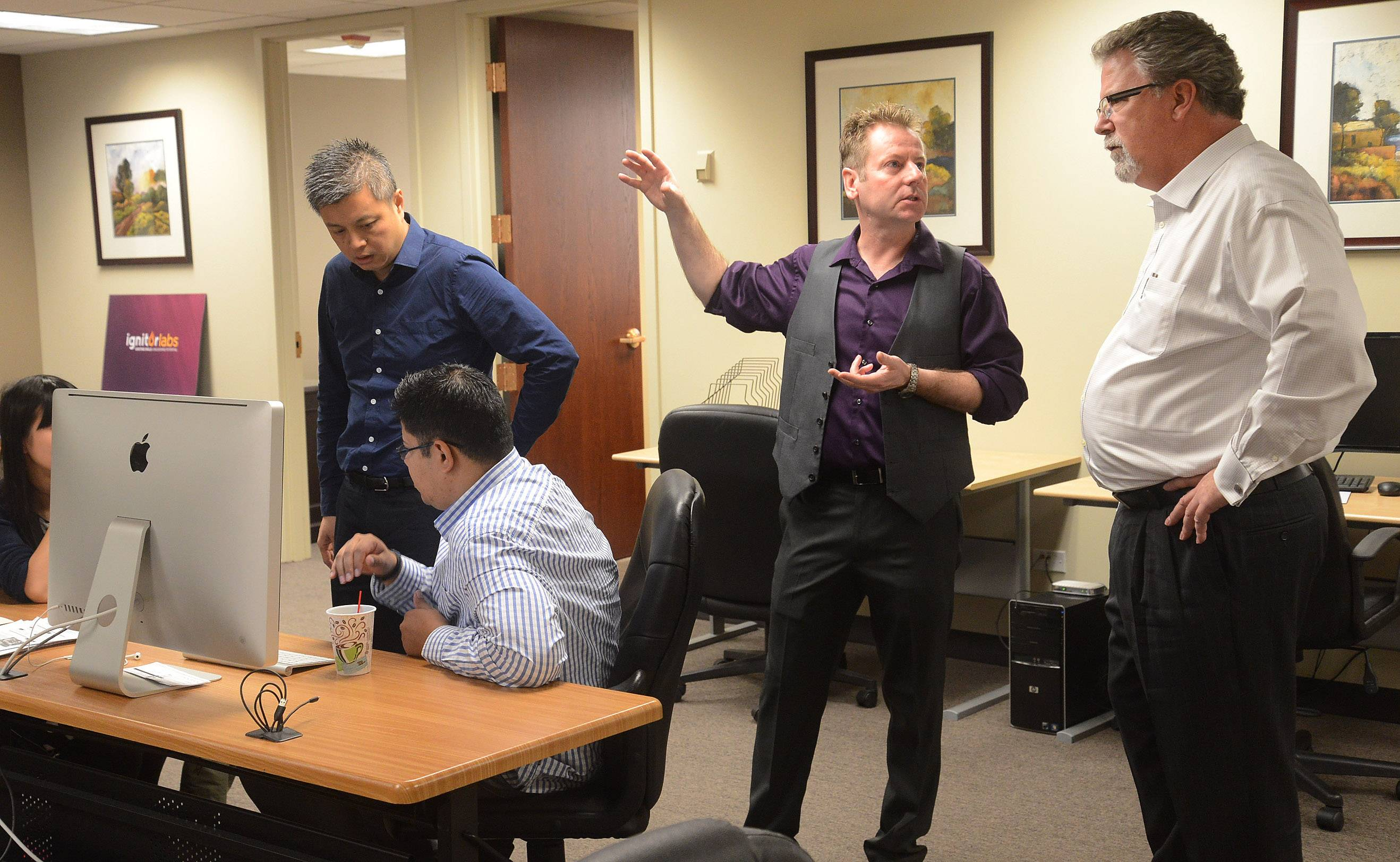 George Nicholson, right, president and CEO of Ignitor Labs, directs some technical staff members at his company's office in Rolling Meadows. Ignitor Labs develops online training programs for technical fields such as commercial food service repair.