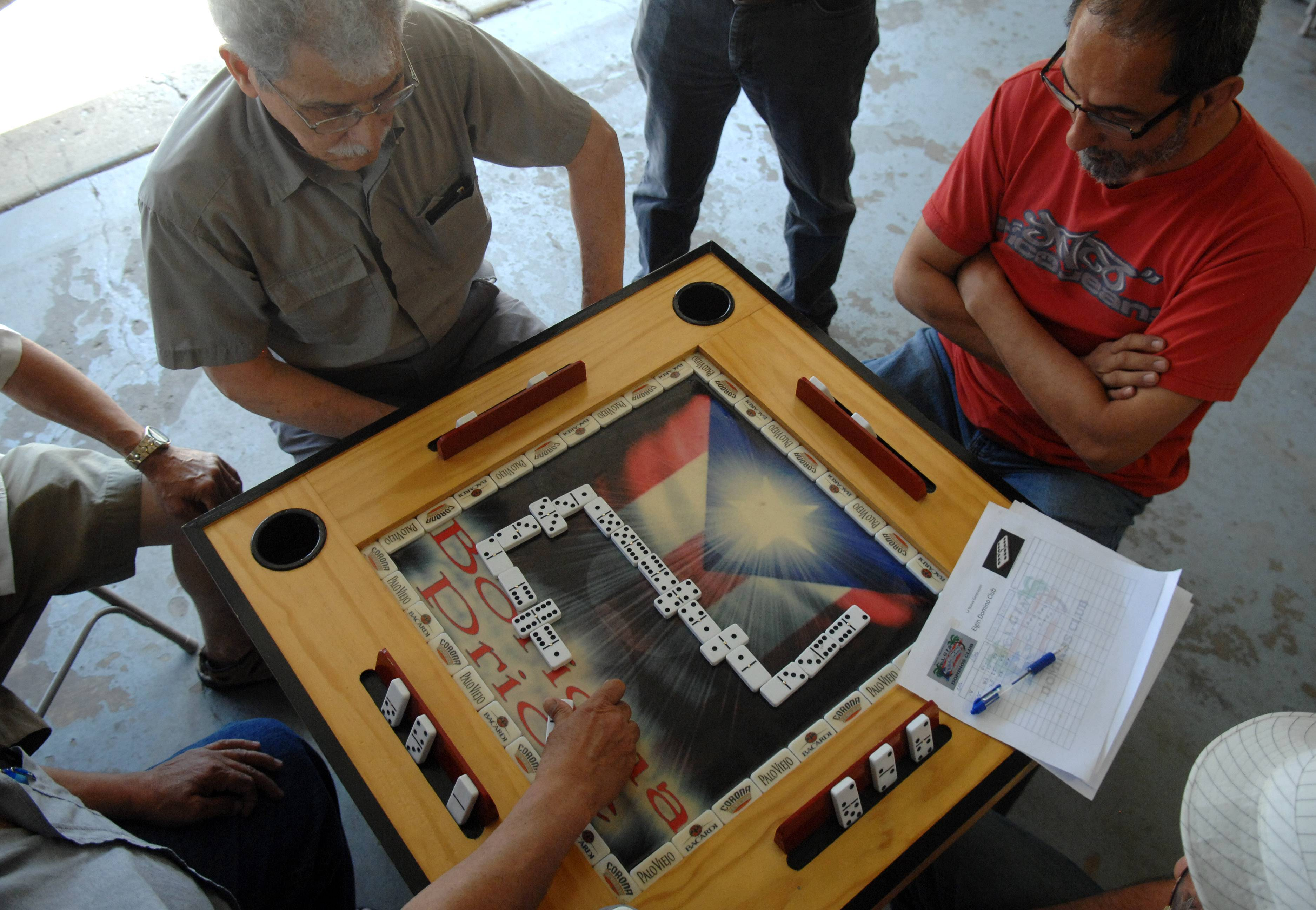 "Members of La Nueva Generacion Elgin Domino Club play in Alfredo ""Cuco"" Garcia's garage in Elgin on a recent Friday. The group has organized a regional domino tournament June 7 in South Elgin."