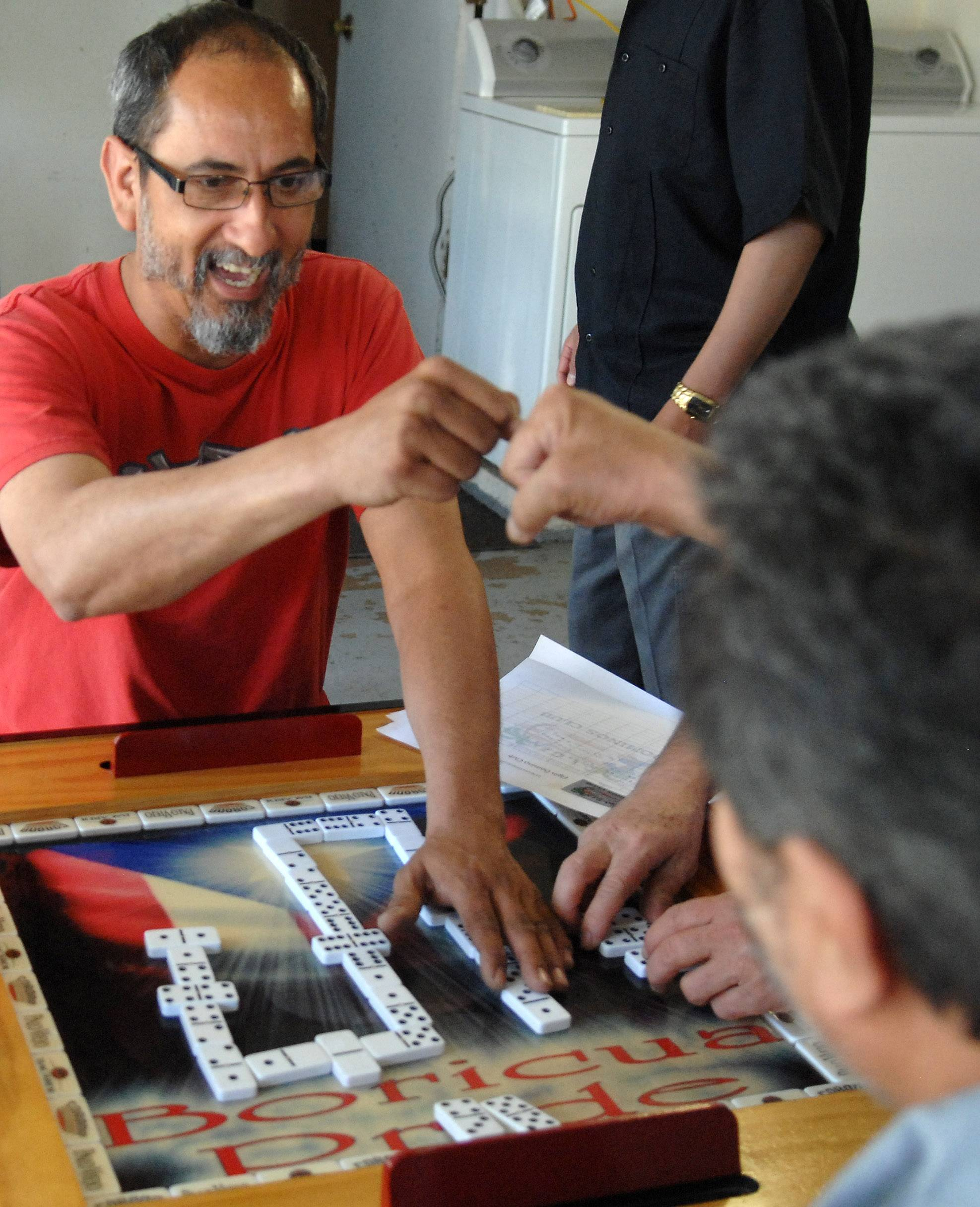 "Fabian Lopez of Elgin fist-bumps his cousin and partner, Donato Lopez, while playing domino at Alfredo ""Cuco"" Garcia's Elgin home."