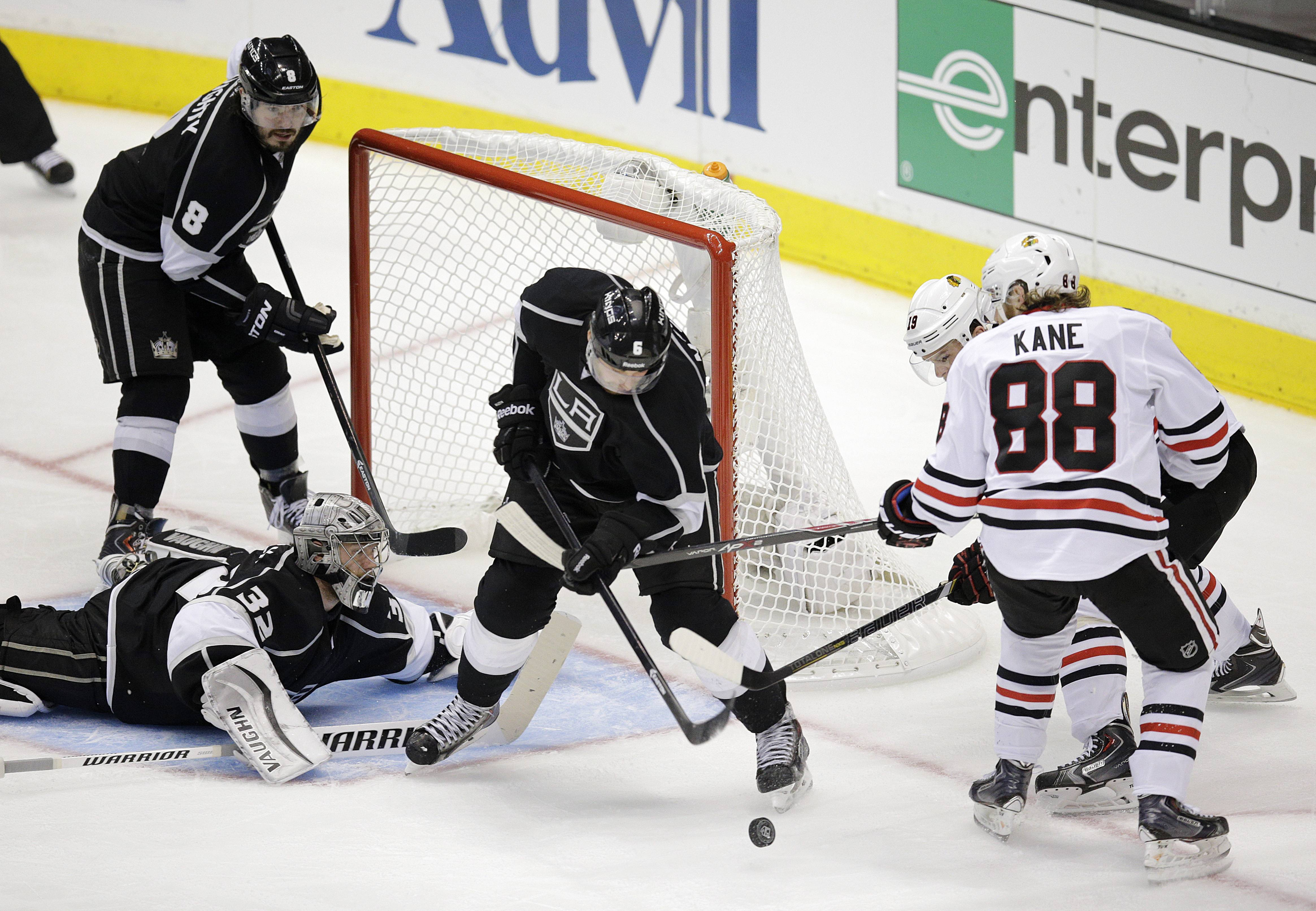 Los Angeles Kings goalie Jonathan Quick (32) watches as Jake Muzzin (6) defends Chicago Blackhawks' Patrick Kane (88) and Jonathan Toews (19) during the third period of Game 4.