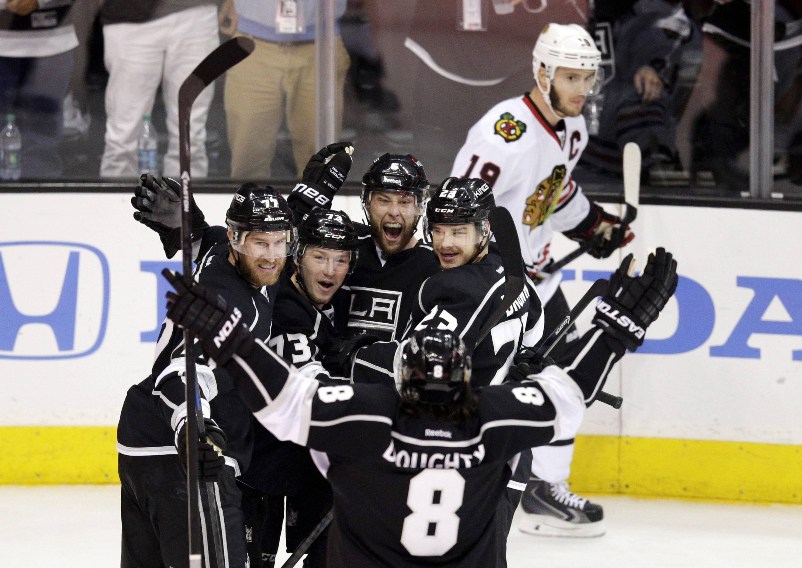 Los Angeles Kings' Jeff Carter (77), Tyler Toffoli (73), Jake Muzzin (6), Dustin Brown (23) and Drew Doughty (8) celebrate a goal by Muzzin as Chicago Blackhawks' Jonathan Toews (19) skates behind them during the first period of Game 4 of the Western Conference finals of the NHL hockey Stanley Cup playoffs on Monday, May 26, 2014, in Los Angeles.