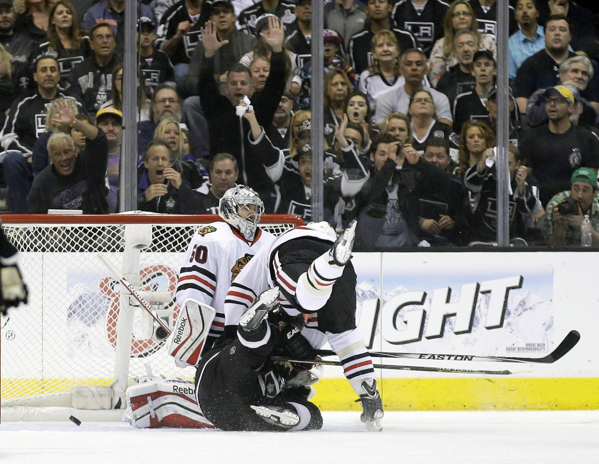 Los Angeles Kings right wing Marian Gaborik, bottom, scores past Chicago Blackhawks goalie Corey Crawford left, and defenseman Brent Seabrook, top, during the first period of Game 4 of the Western Conference finals of the NHL hockey Stanley Cup playoffs in Los Angeles, Monday, May 26, 2014.