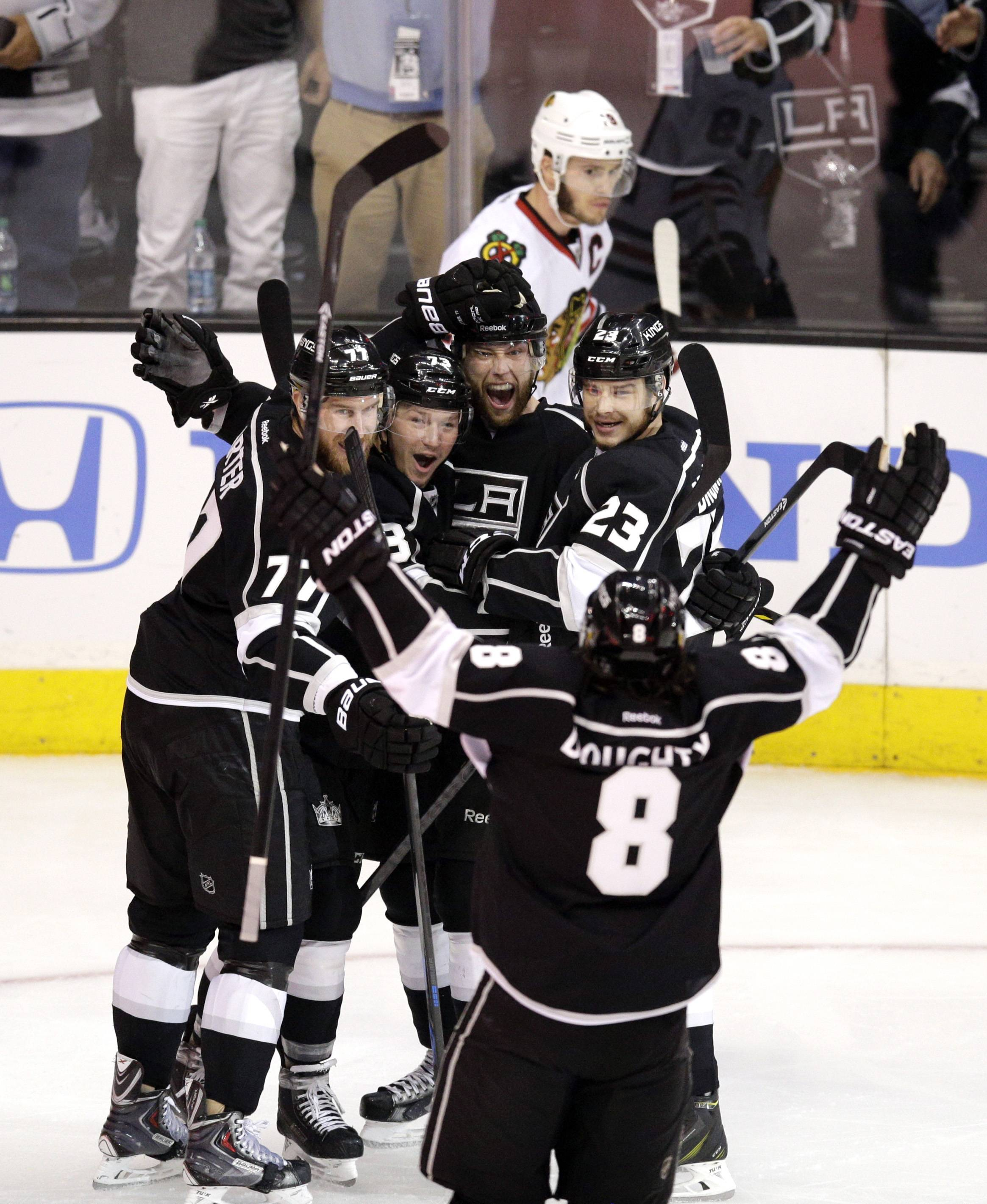 Los Angeles Kings' Jeff Carter (77), Tyler Toffoli (73), Jake Muzzin (6), Dustin Brown (23) and Drew Doughty (8) celebrate a goal by Muzzin as Chicago Blackhawks' Jonathan Toews skates behind them during the first period of Game 4 of the Western Conference finals of the NHL hockey Stanley Cup playoffs on Monday, May 26, 2014, in Los Angeles.