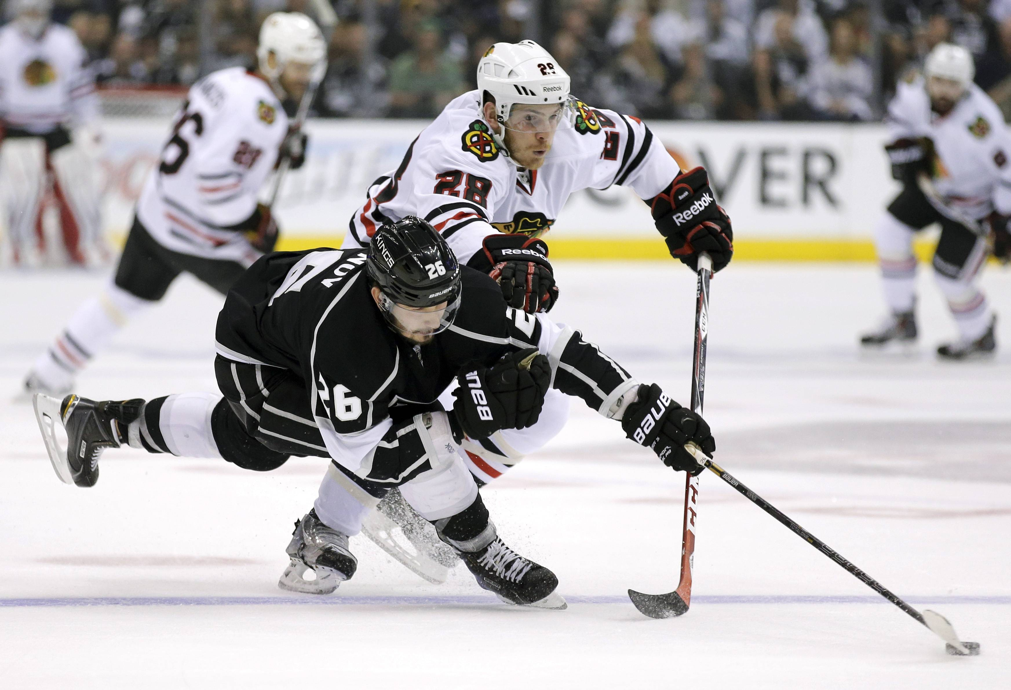 Los Angeles Kings defenseman Slava Voynov, left, knocks the puck away from Chicago Blackhawks right wing Ben Smith during the first period of Game 4 of the Western Conference finals of the NHL hockey Stanley Cup playoffs in Los Angeles, Monday, May 26, 2014.