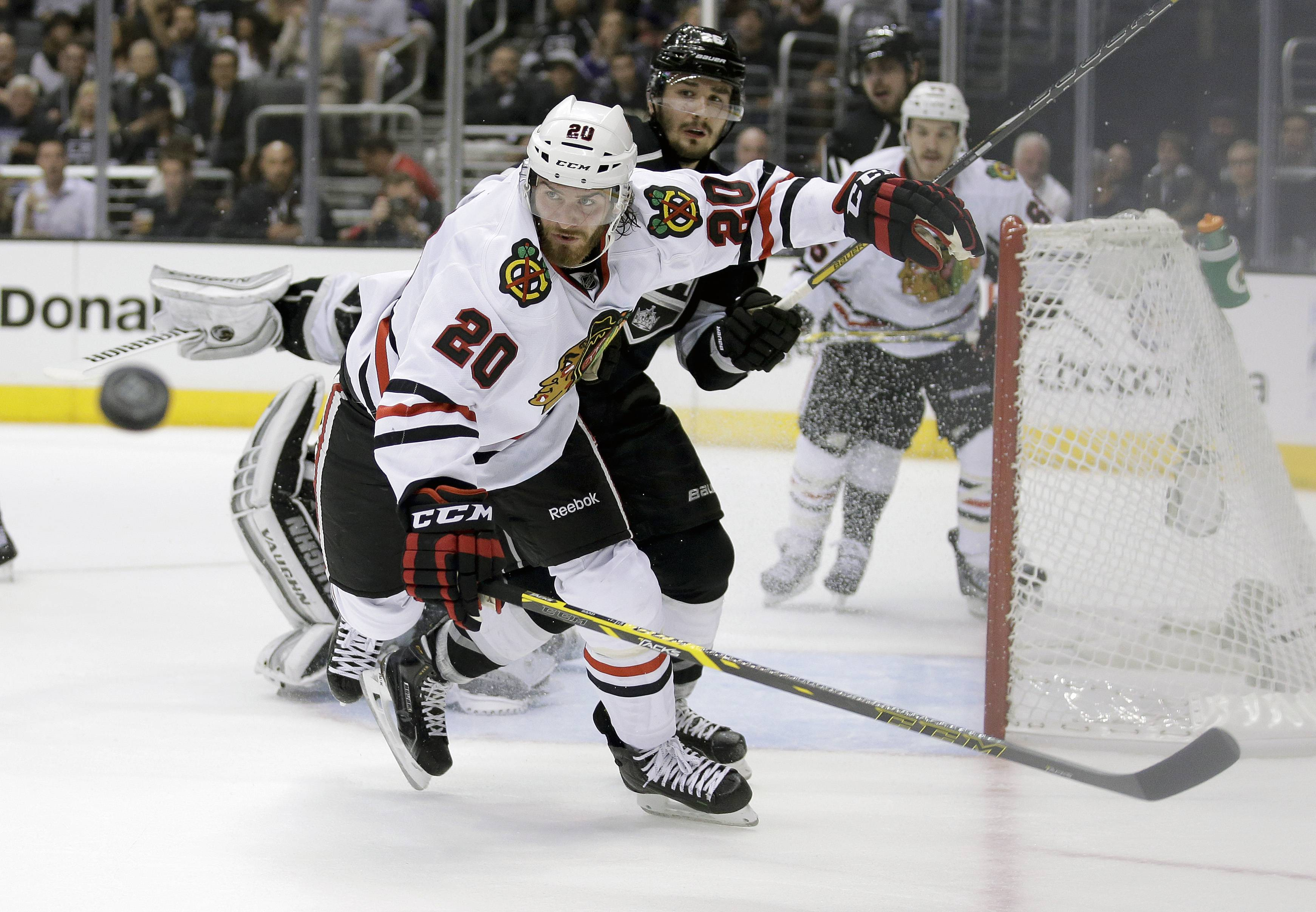 Chicago Blackhawks left wing Brandon Saad, left, and Los Angeles Kings defenseman Slava Voynov go after the puck during the first period of Game 4 of the Western Conference finals of the NHL hockey Stanley Cup playoffs in Los Angeles, Monday, May 26, 2014.