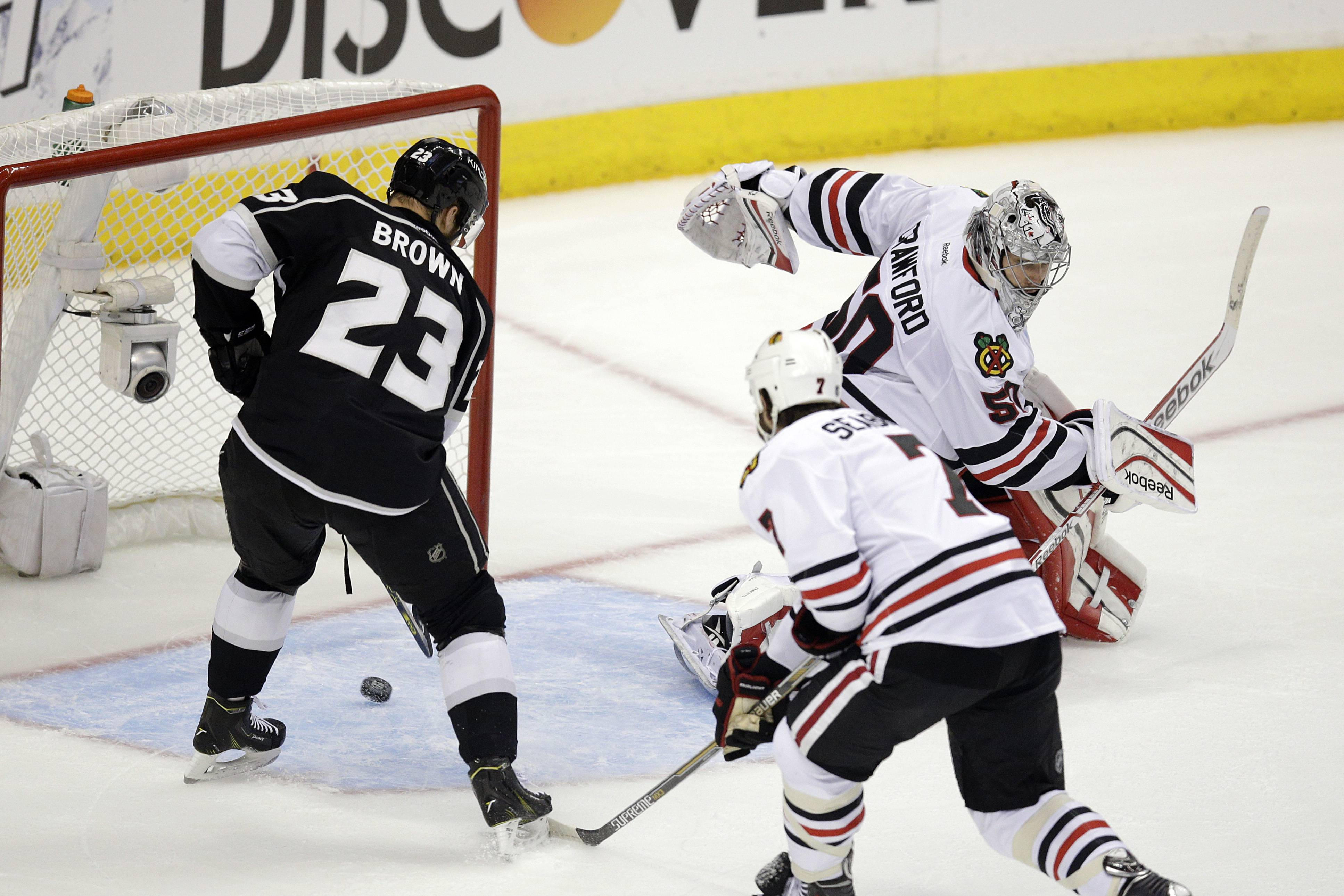 Los Angeles Kings' Dustin Brown, left, scores against Chicago Blackhawks goalie Corey Crawford, right, as Blackhawks' Brent Seabrook skates near during the first period of Game 4 of the Western Conference finals of the NHL hockey Stanley Cup playoffs on Monday, May 26, 2014, in Los Angeles.