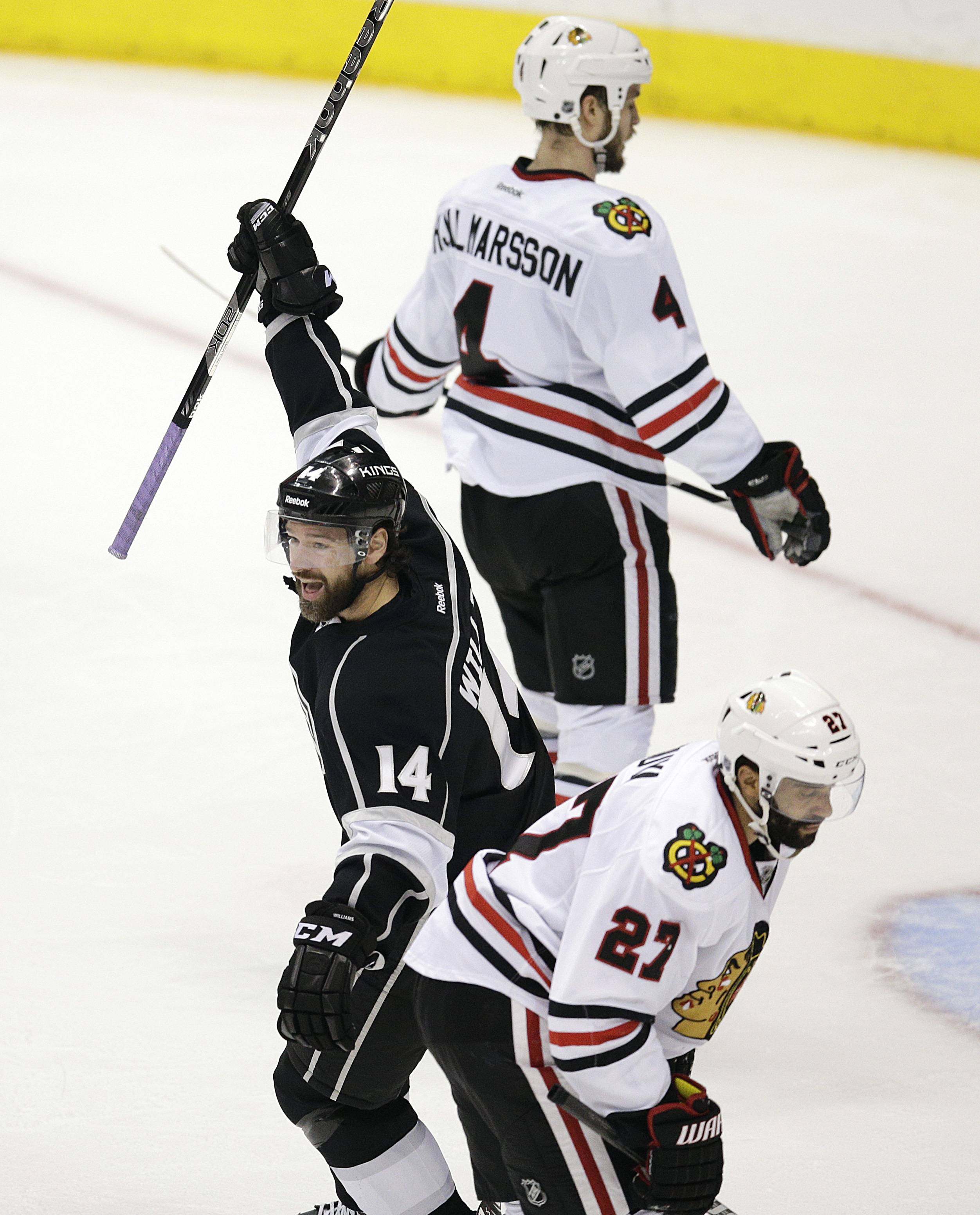 Los Angeles Kings' Justin Williams, center, celebrates a goal by Drew Doughty as he skates past Chicago Blackhawks Johnny Oduya, bottom, of Sweden, and Niklas Hjalmarsson, of Sweden, during the second period of Game 4 of the Western Conference finals of the NHL hockey Stanley Cup playoffs on Monday, May 26, 2014, in Los Angeles.