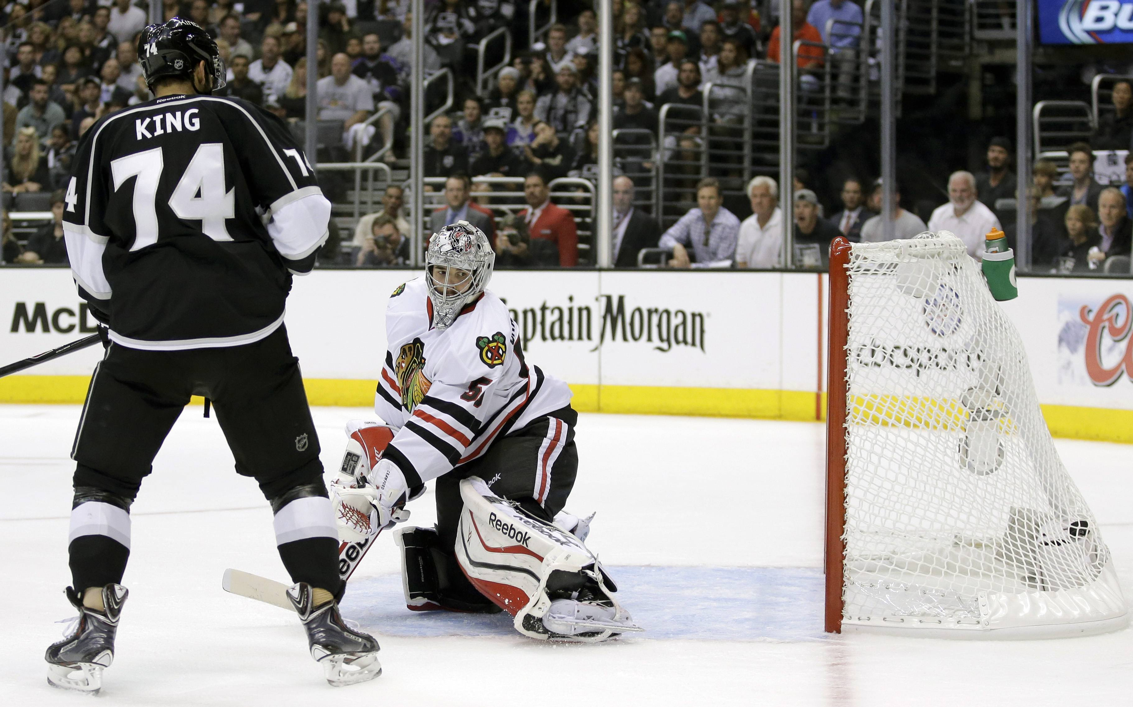 Los Angeles Kings left wing Dwight King, left, and Chicago Blackhawks goalie Corey Crawford watch defenseman Drew Doughty's goal during the second period of Game 4 of the Western Conference finals of the NHL hockey Stanley Cup playoffs in Los Angeles, Monday, May 26, 2014.