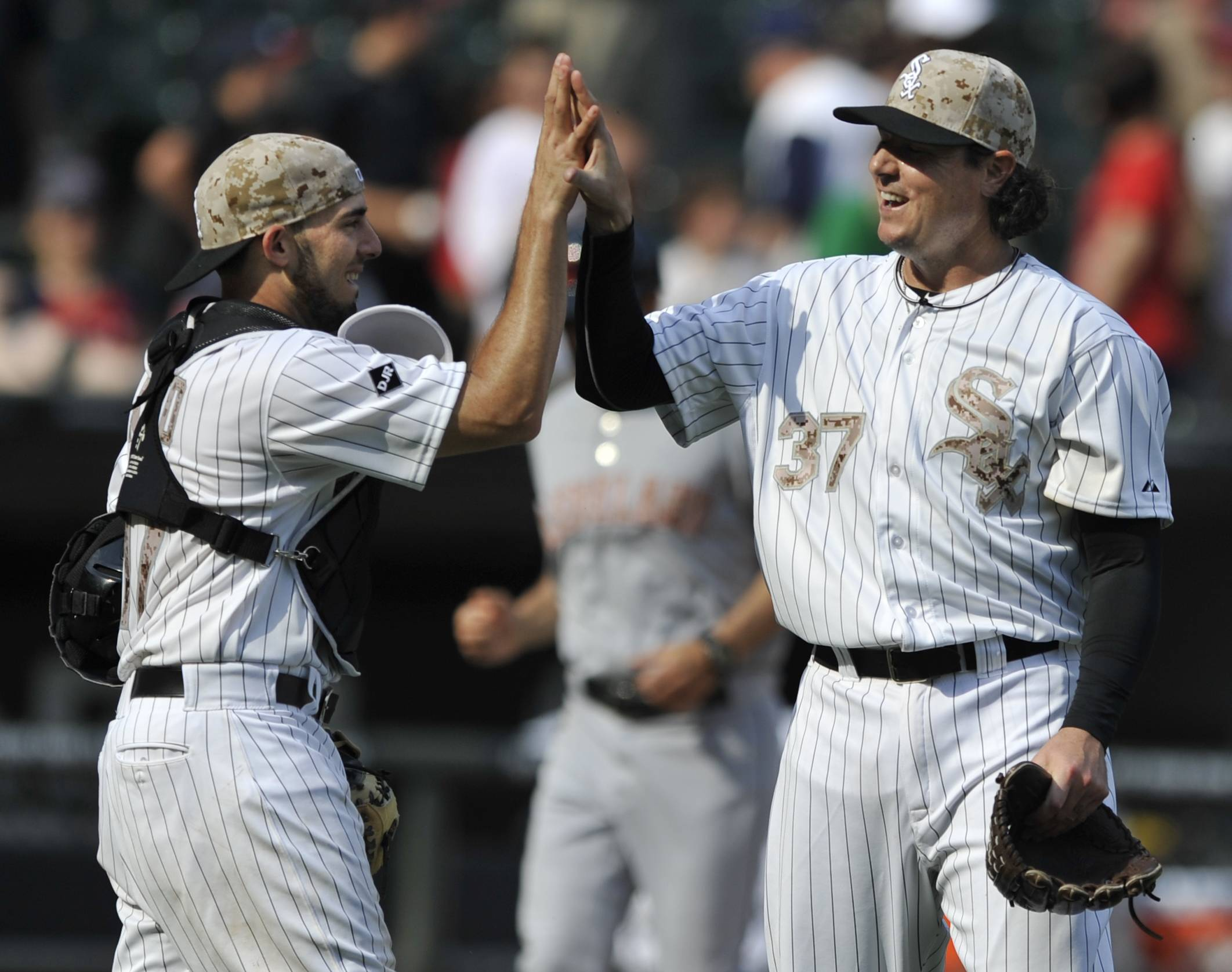 Chicago White Sox closing pitcher Scott Downs (37), celebrates with catcher Adrian Nieto, left, after defeating the Cleveland Indians 6-2 during a baseball game in Chicago, Monday.