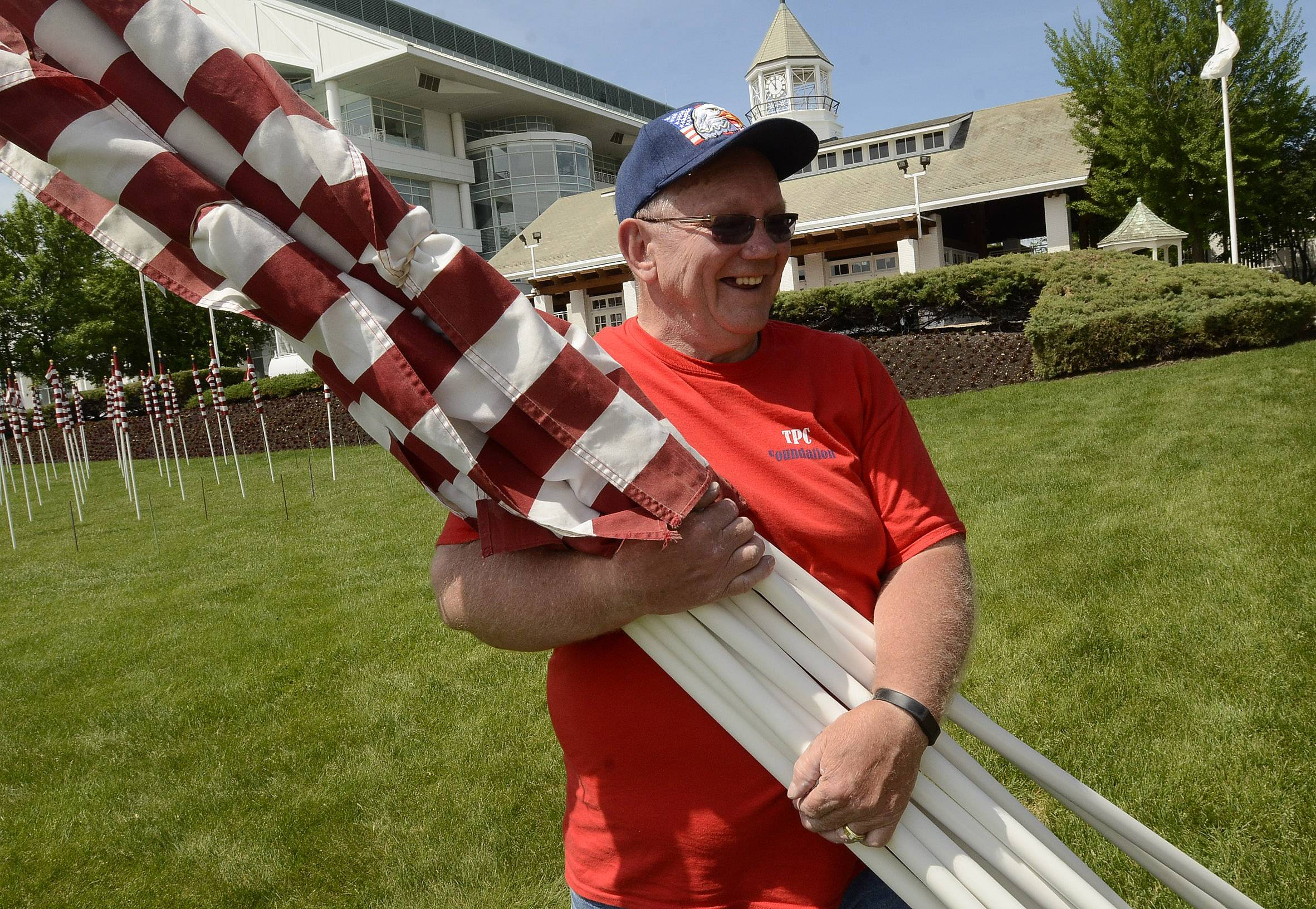 "True Patriots Care Foundation President Jerry Christopherson, along with his volunteers, remove the 323 American flags that made up the ""Field of Honor"" at Arlington International Racecourse. The flags stood at the track over the Memorial Day weekend in honor of Illinois soldiers killed since Sept. 11, 2001."