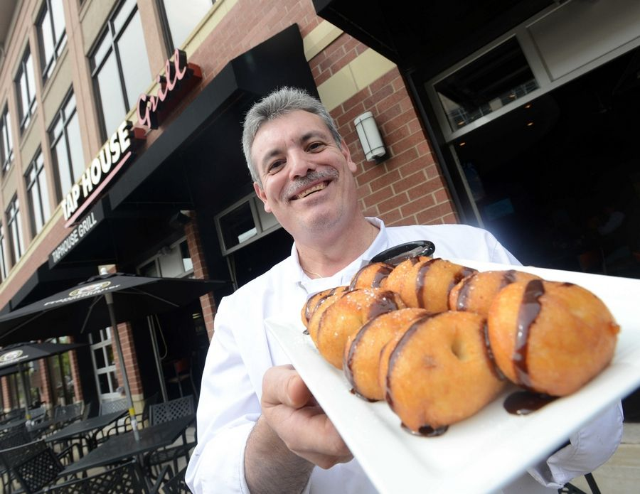 Chef Guilermo Quezada displays the homemade Sticky Caramel-Chocolate Donuts at the Tap House Grill in Des Plaines.