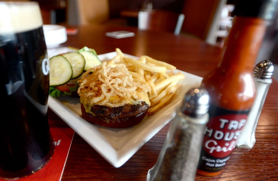 A Tipsy Stout Burger comes topped with haystring onions at the Tap House Grill in Des Plaines.