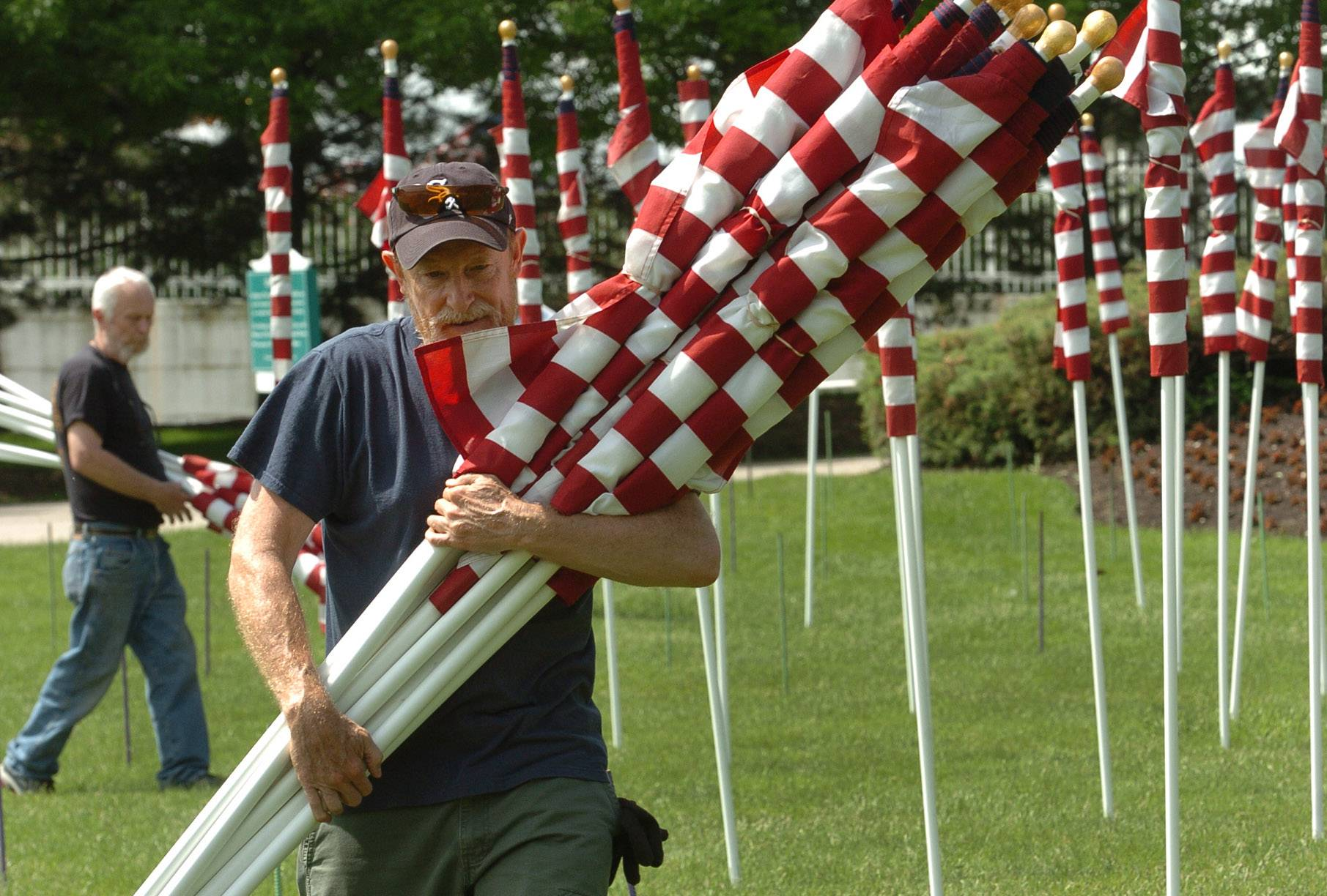 "True Patriots Care Foundation member Frank LeBeau, from Cary, along with fellow volunteers, remove the 323 American flags that made up the ""Field of Honor"" at Arlington International Racecourse. The flags stood at the track over the Memorial Day weekend in honor of Illinois soldiers killed since Sept. 11, 2001."