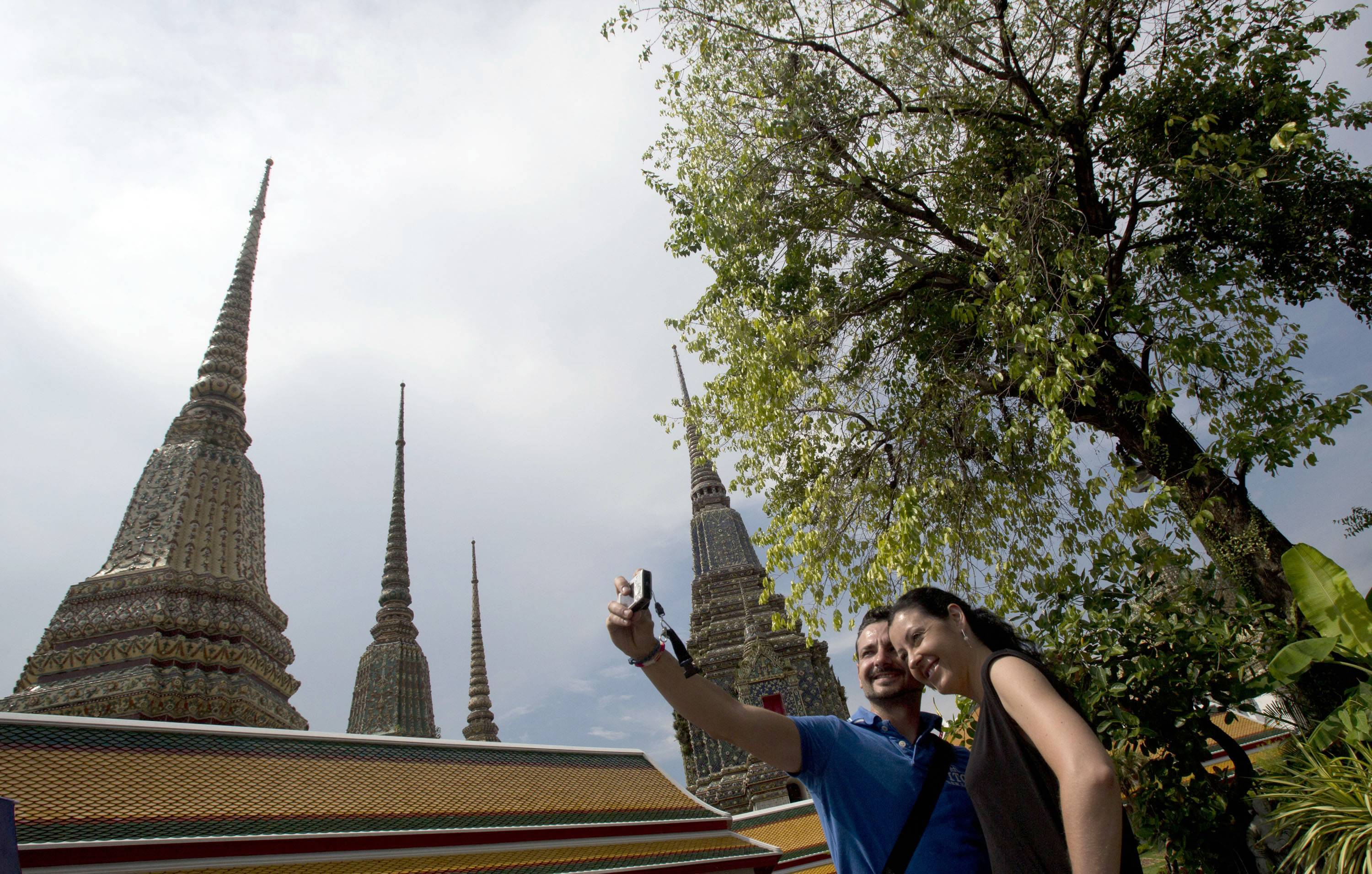 A couple of Western tourists snap a souvenir photo at a Wat Pho temple in Bangkok, Thailand Tuesday, May 27, 2014. The drama of Thailand's military takeover has played out mainly in the political arena. The main impact on visitors for now is a 10 p.m. curfew.