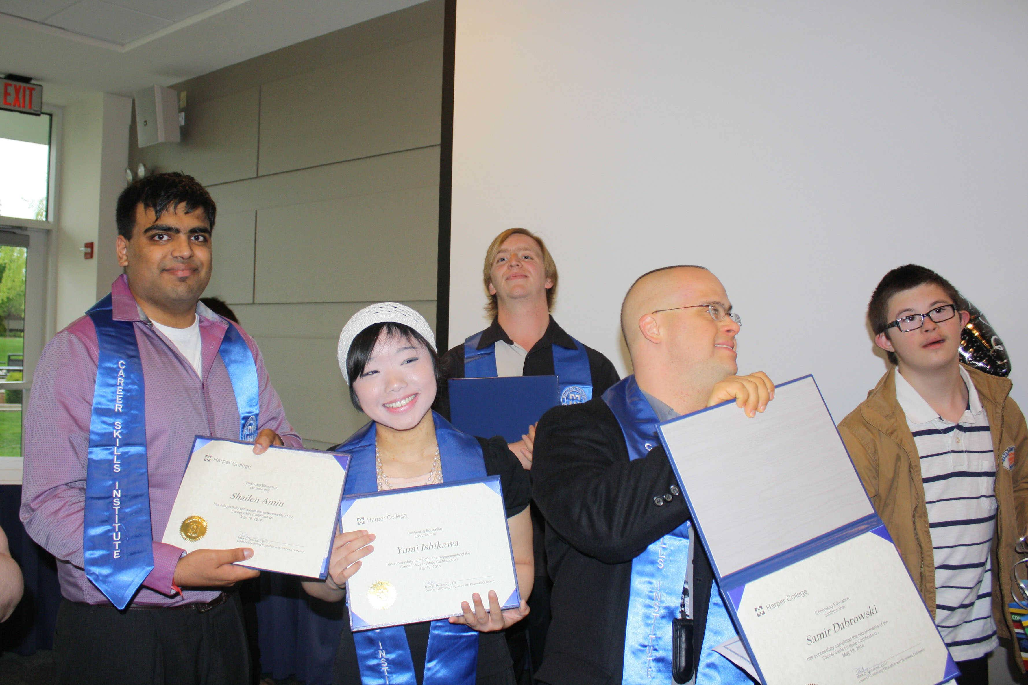 Graduates display their certificates, including Shailen Amin of Schaumburg, Yumi Ishikawa of Northbrook, Adam Pierce of Arlington Heights, and Samir Dabrowski of Mount Prospect.