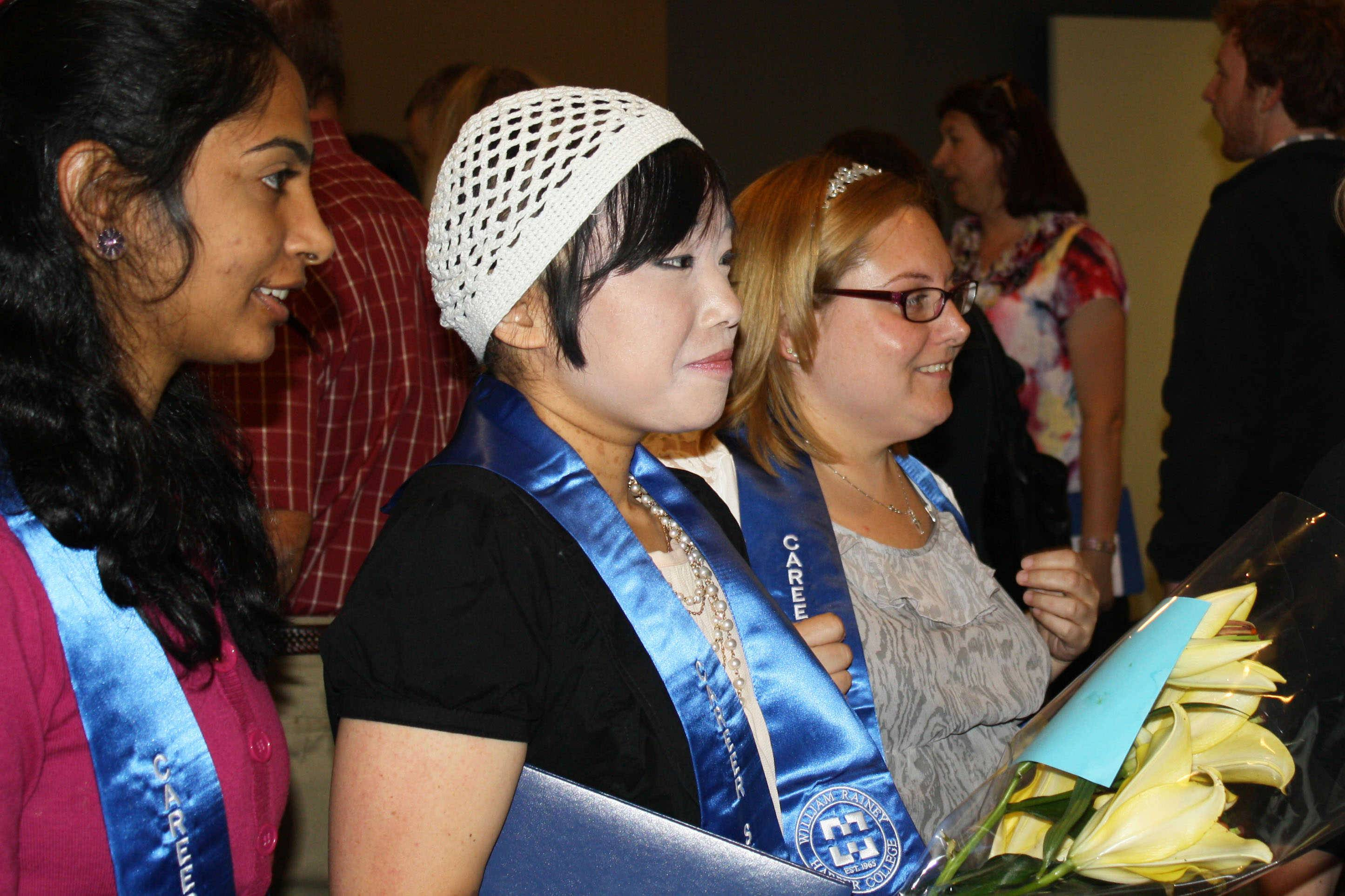 Nikhita Devulapally of Roselle, Yumi Ishikawa of Northbrook and Amy Thiede of Elk Grove Village listen to the speakers during the graduation ceremony.