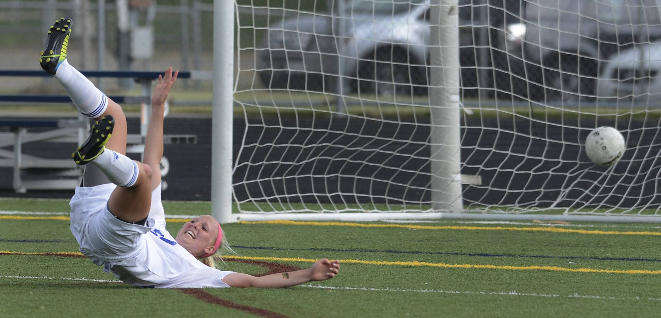 Sophie Pohl of St. Charles North falls backward as she scores a first-half goal against St. Charles East during the Conant sectional semifinal in Hoffman Estates Tuesday.