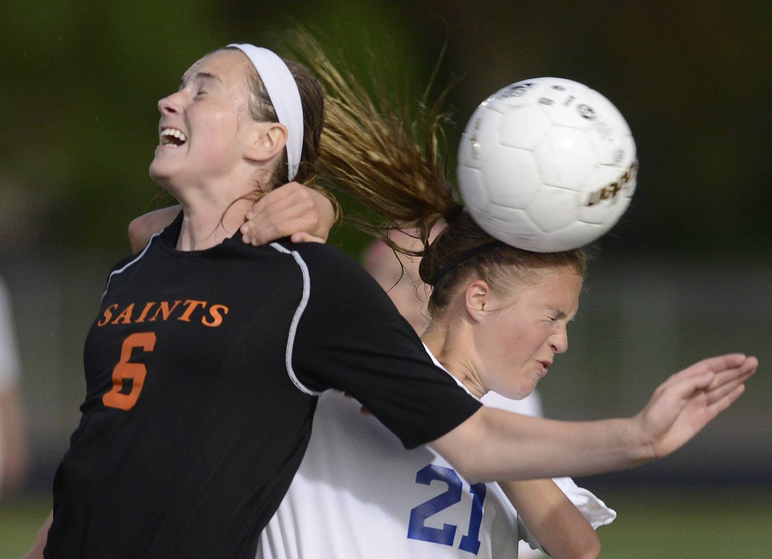 Joe Lewnard/jlewnard@dailyherald.comKelli Santo Paolo, left, of St. Charles East and Amanda Czerniak of St. Charles North become entangled as they leap for a header during the Conant sectional semifinal in Hoffman Estates Tuesday.