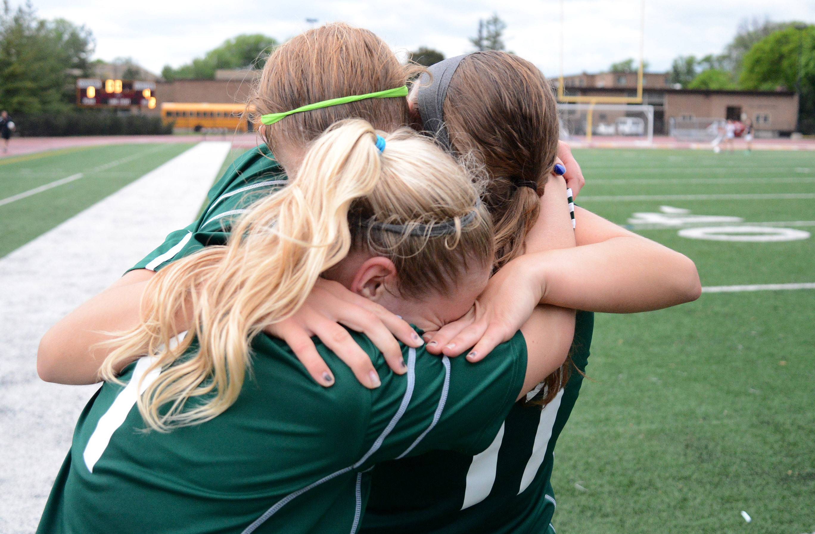St. Edward seniors Corey Lepoudre, (center, bottom) Emily Witt (center top) and Allison Kruk, (right) celebrate their Class 1A supersectional win over Chicago Latin at Concordia University in River Forest on Tuesday.