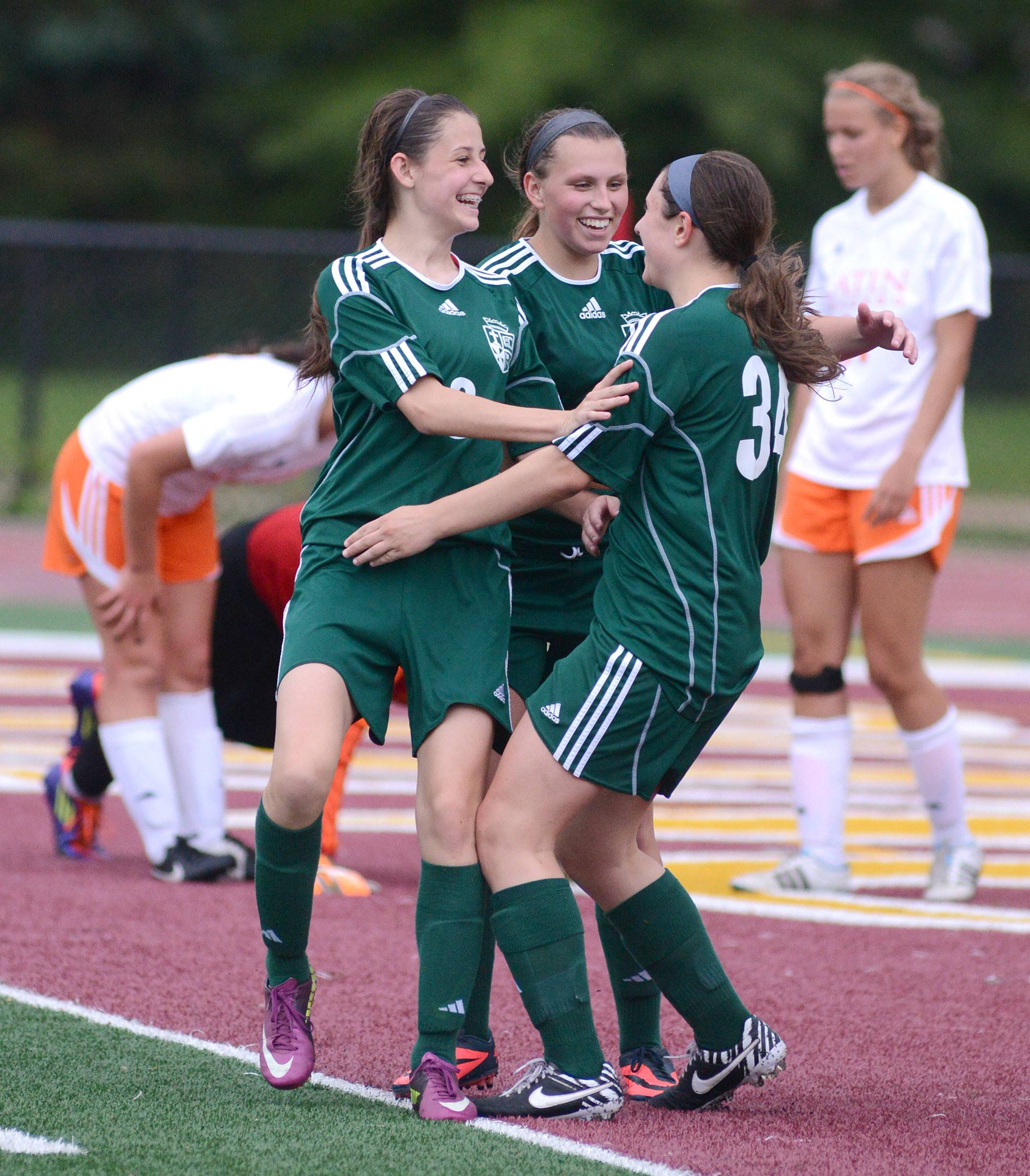 St. Edward's Chelsea Gana, left, Allison Kruk, center, rushes to congratulate Alex Zeller on her goal against Chicago Latin in the second half of the Class 1A supersectional at Concordia University in River Forest on Tuesday.