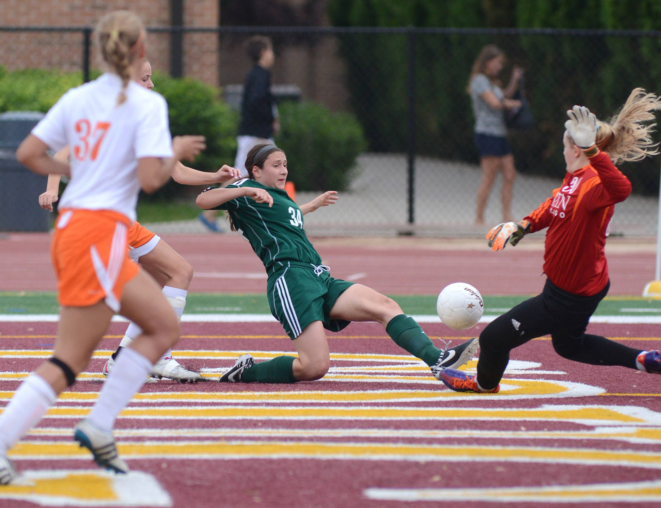 St. Edward's Alex Zeller kicks the ball into the net for a goal and slides into Chicago Latin's goalie Catie Cronister in the first half of the Class 1A supersectional at Concordia University in River Forest on Tuesday.