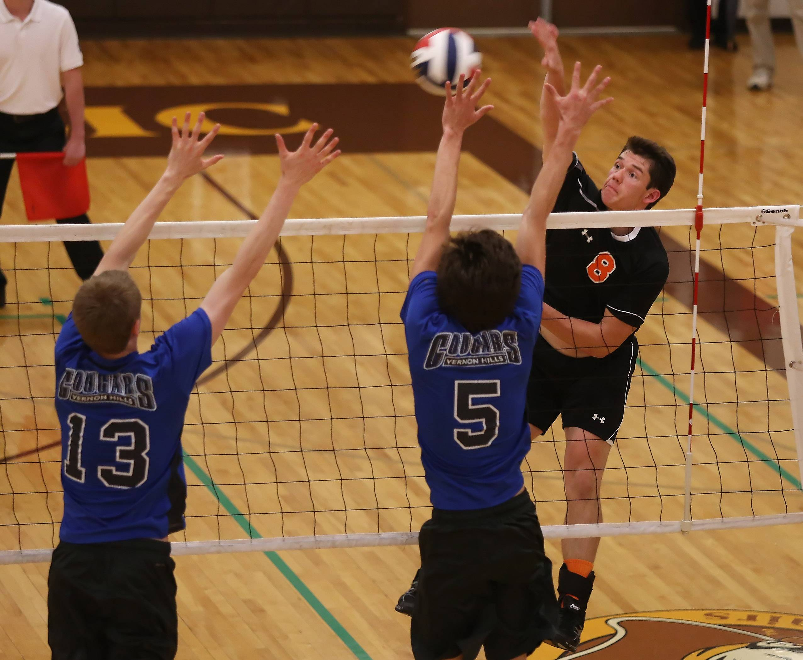 Libertyville hitter Chris Akers attacks against Vernon Hills players Max Spiglanin and Tyler Small, right, during regional semifinal play Tuesday at Carmel.