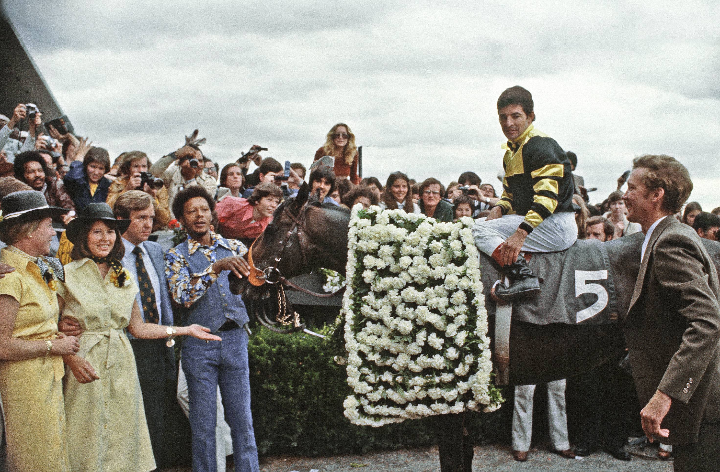 In this June 1, 1977 file photo, jockey Jean Cruguet sits on Seattle Slew in the winners circle after winning  Belmont Stakes in Elmont, N.Y.  Standing second from left is Karen Taylor, owner of Seattle Slew. Third from left is her husband, Mickey. California Chrome will try to win the Triple Crown at the Belmont Stakes on June 7.