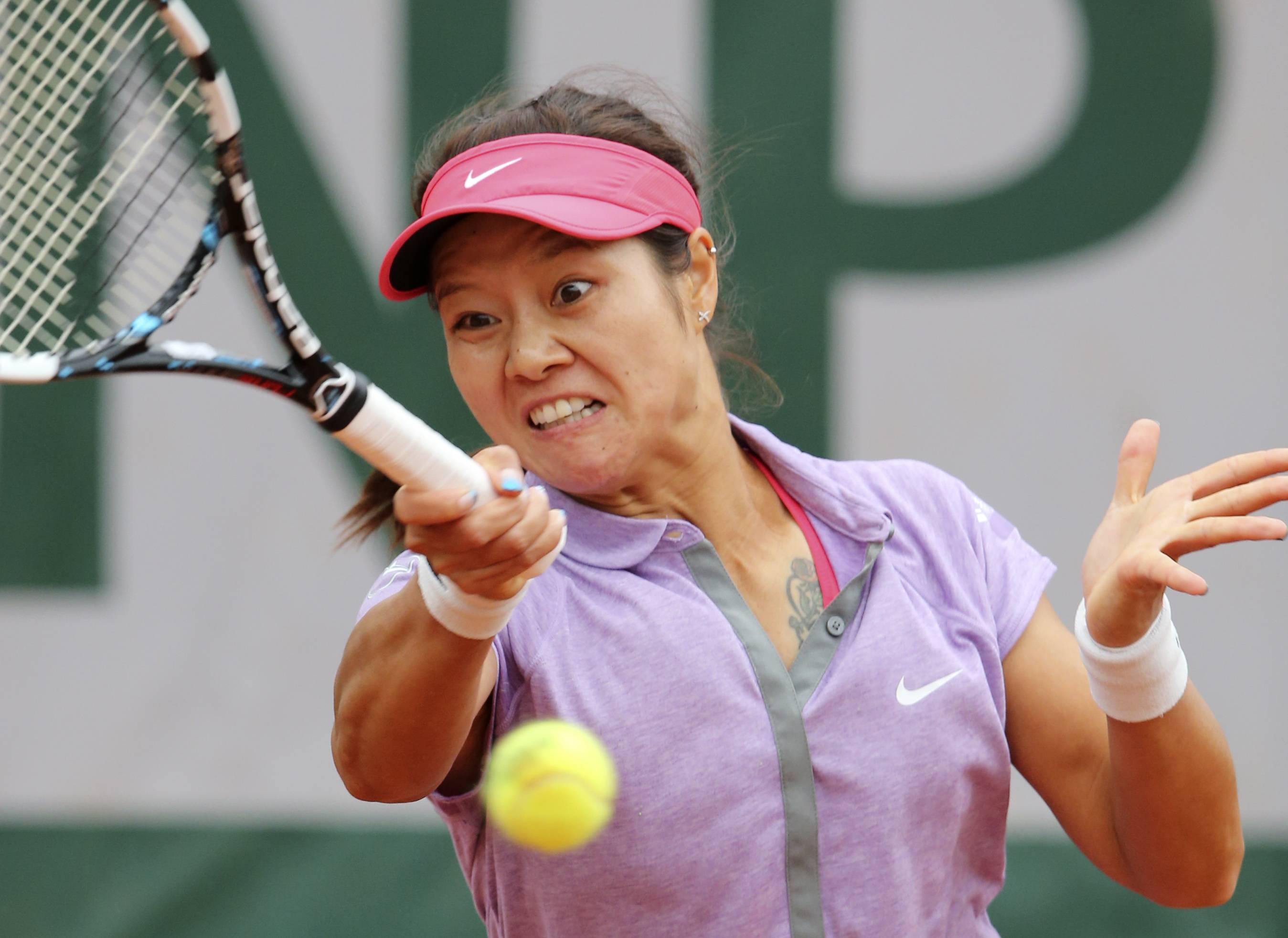 Li Na hits a return against France's Kristina Mladenovic Monday during their first round match in the French Open tennis tournament at Roland Garros stadium in Paris.