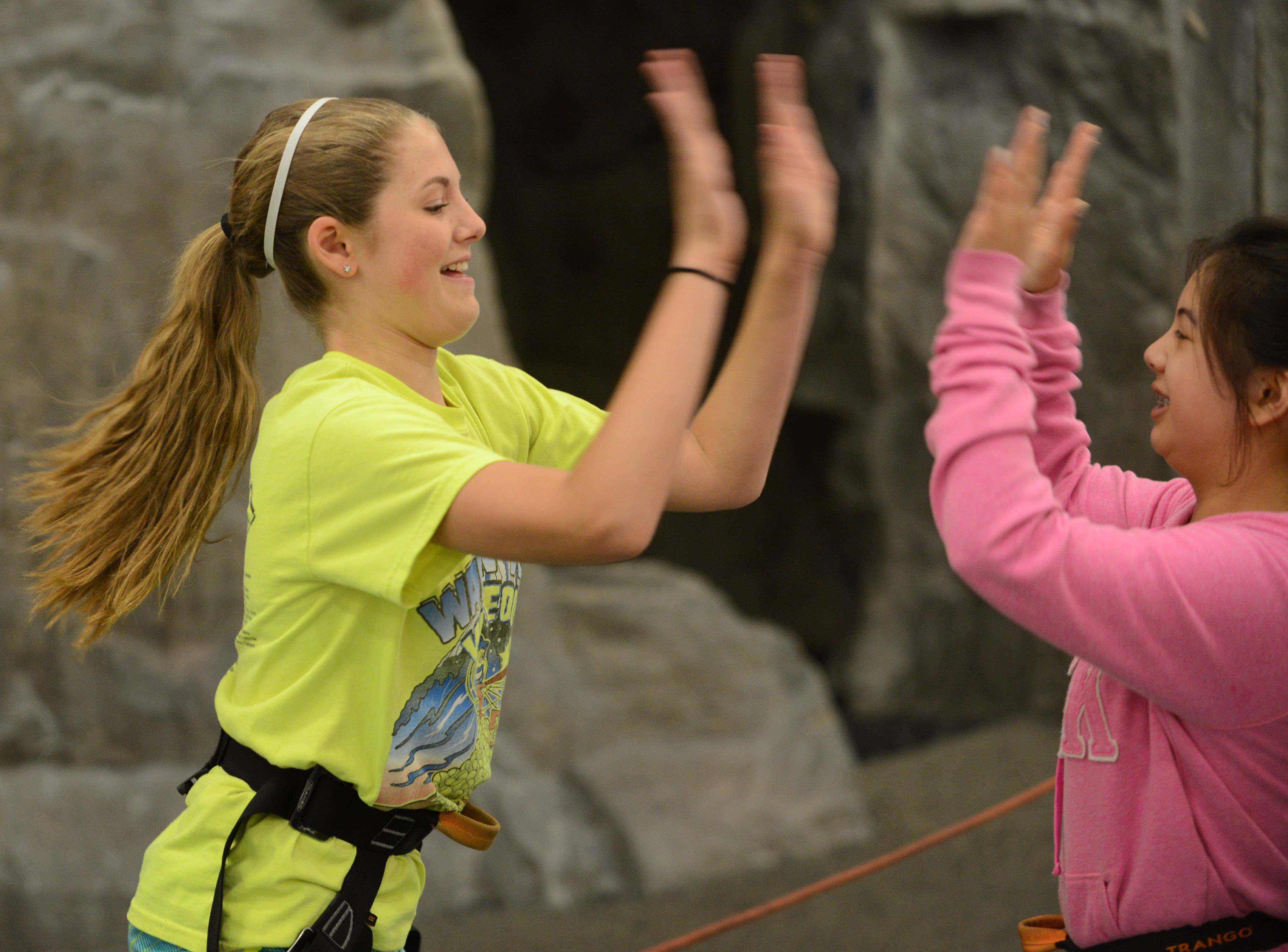 Woodland Middle School seventh grade student Kayla Nommensen, left, gives high-fives to schoolmate Julia De La Cruz after climbing the wall at the Libertyville Sports Complex on Wednesday. Two hundred students spent the day at the complex participating in a variety of sports and activities.