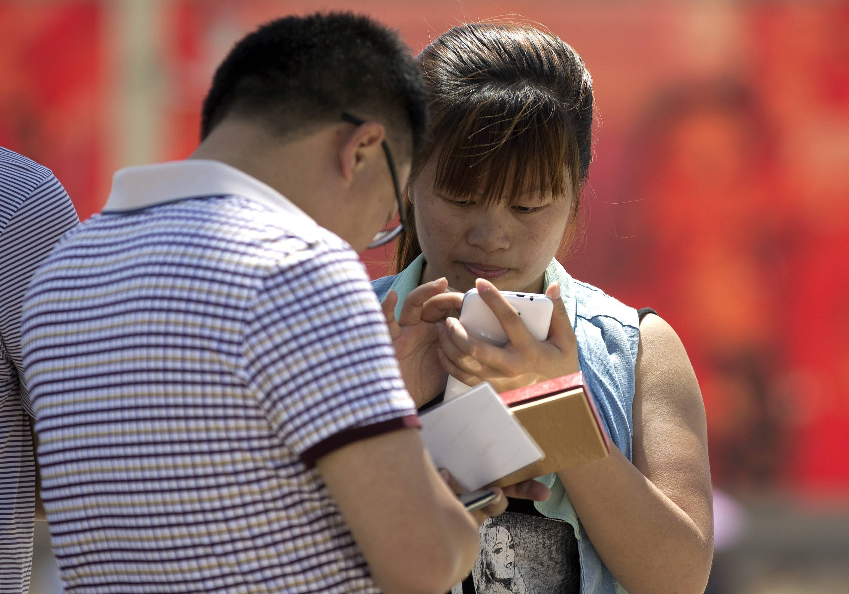Chinese people use their smartphone on Tiananmen Square in Beijing, China Wednesday.